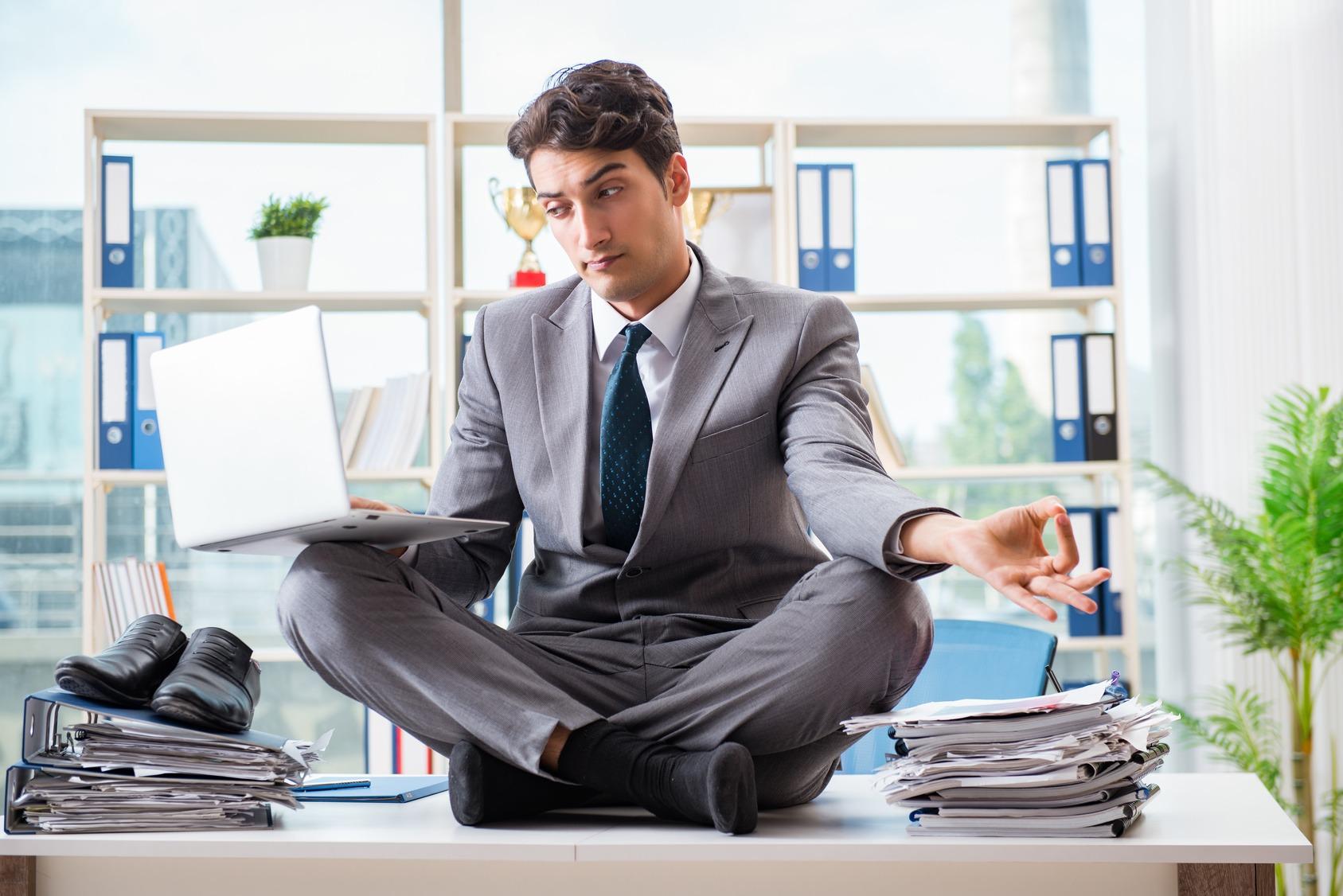 Geschäftsmann sitzt konzentriert im Schneidersitz auf seinem Schreibtisch.