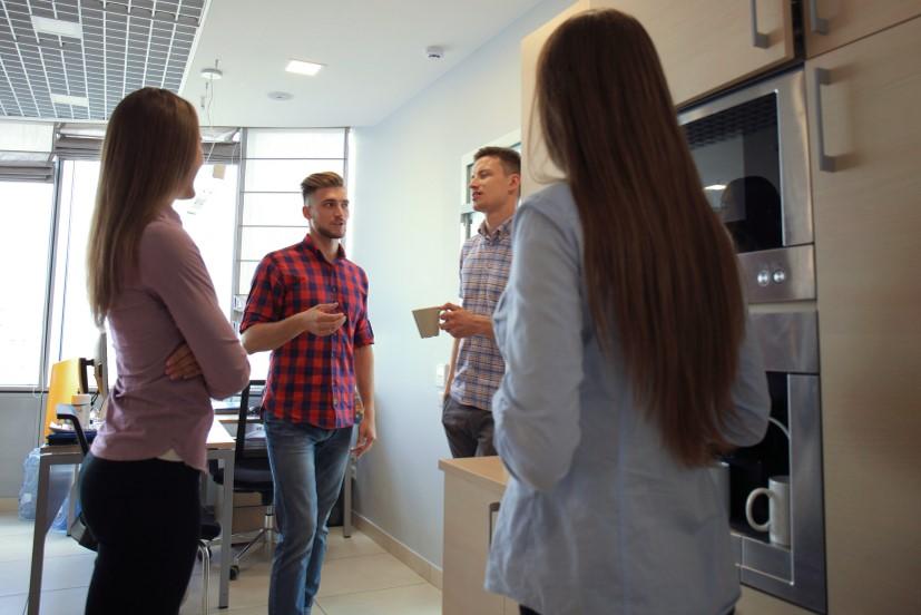 Eine Gruppe Kollegen beim Small Talk in der Büroküche