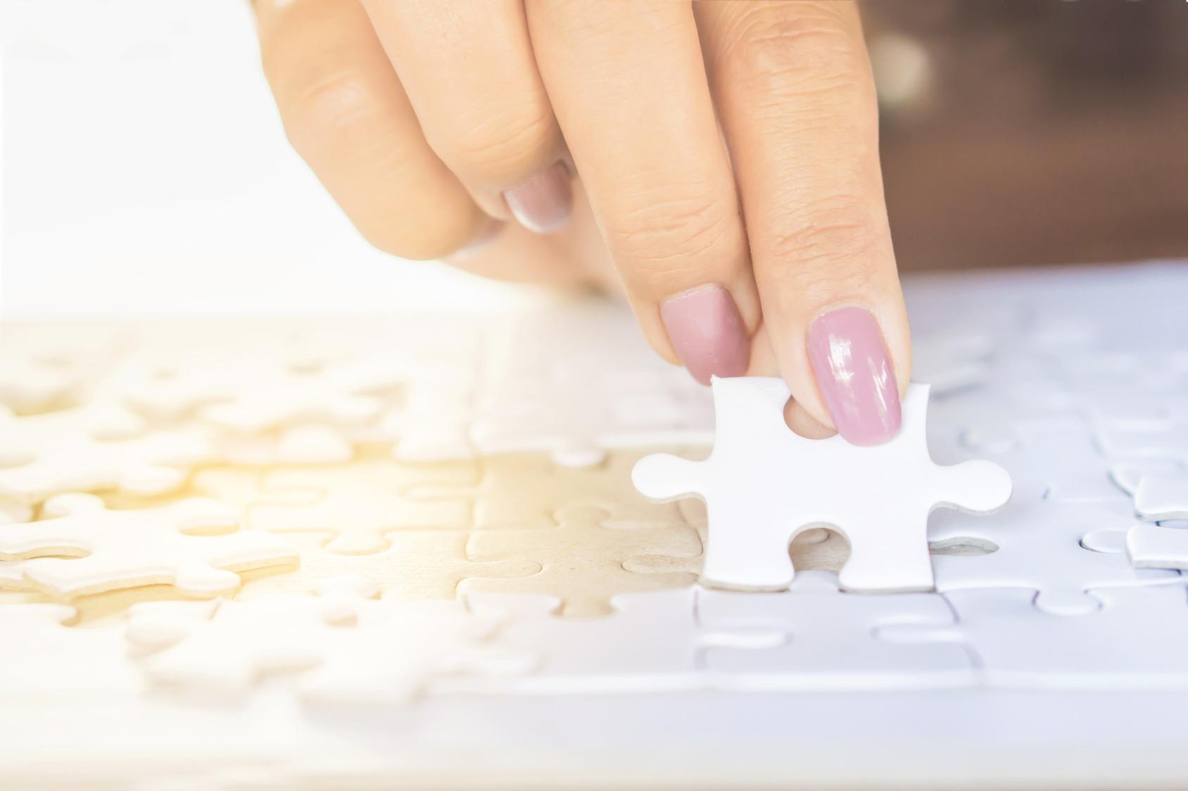 Nahaufnahme einer Frauenhand die ein Puzzelteil in ein weißes Puzzle einfügt.