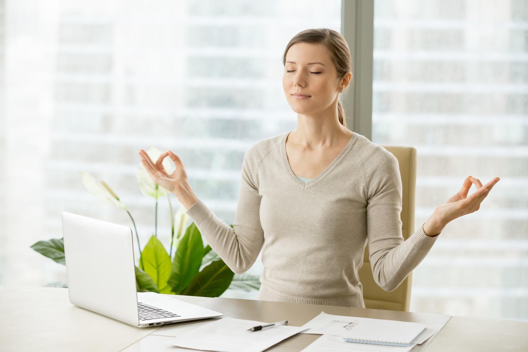 Eine entspannte Geschäftsfrau macht Atemübungen zur besseren Konzentration an ihrem Arbeitsplatz.