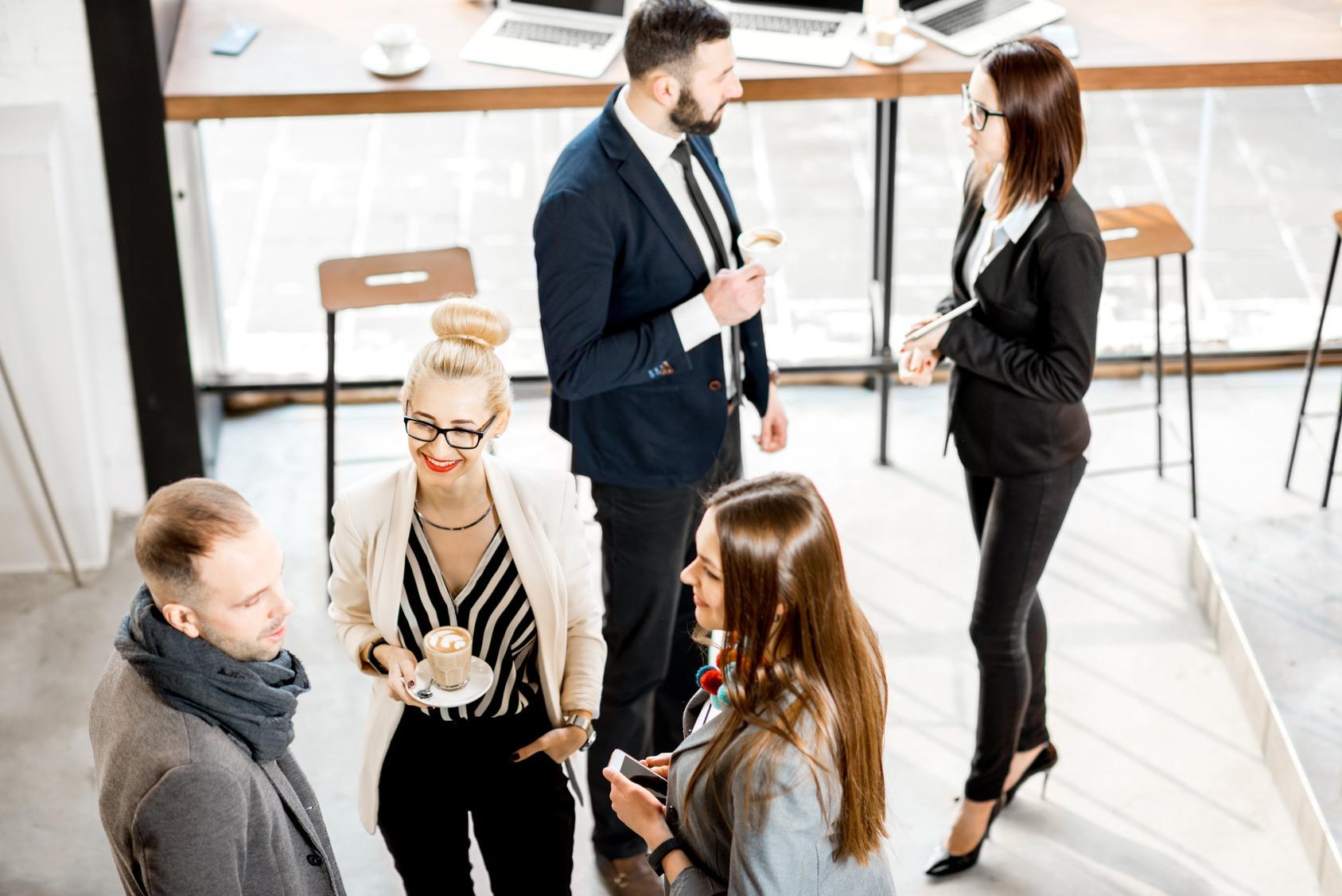 Eine Gruppe Geschäftsleute beim Smalltalk in einem Coworking Space.