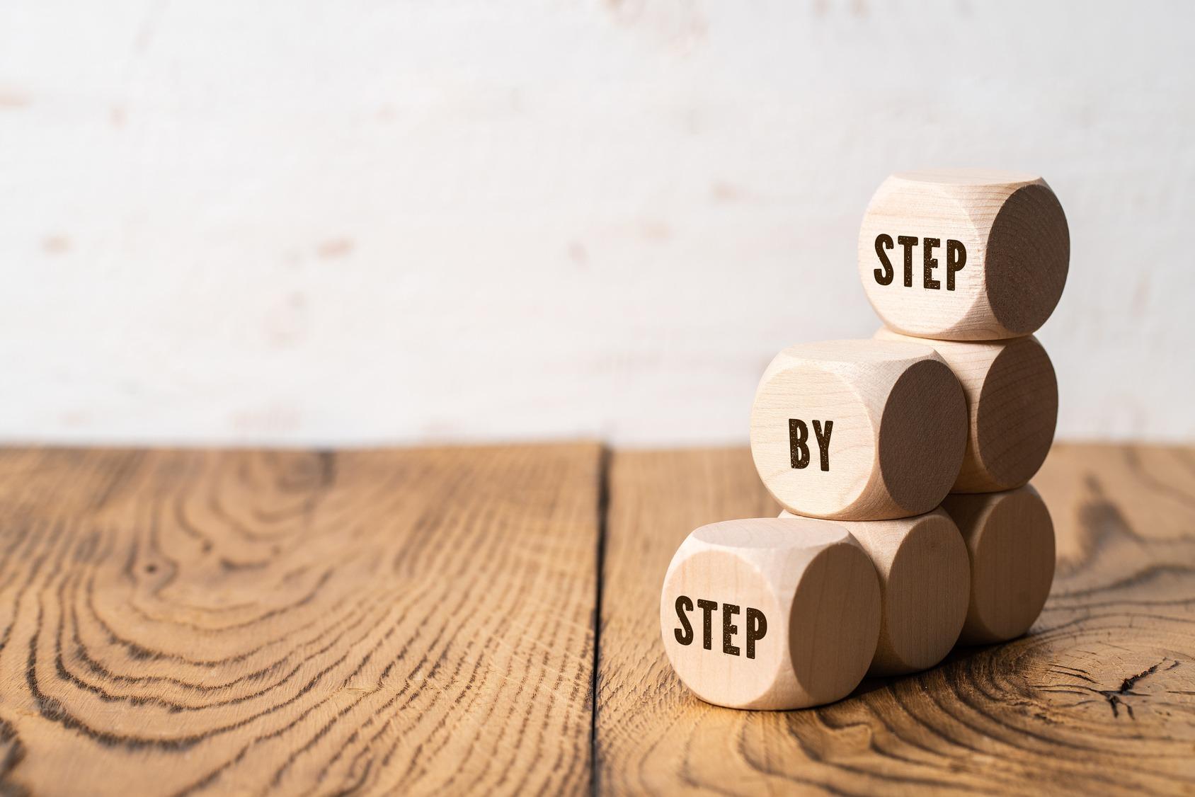 """Drei Stapel Holzwürfel auf einem Holztisch auf den aufsteigend, geschrieben steht, """"step-by-step""""."""