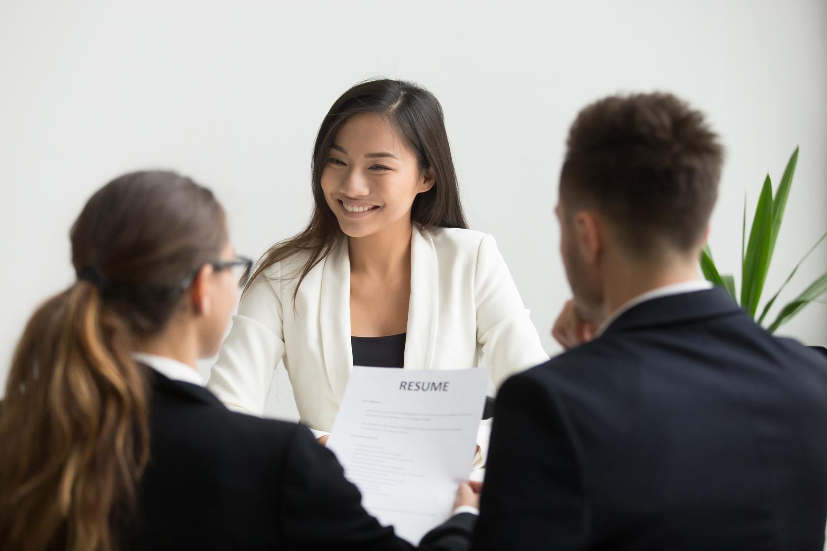 Eine junge Bewerberin ist selbstsicher beim Vorstellungsgespräch weil sie ihre Rhetorik geübt hat.