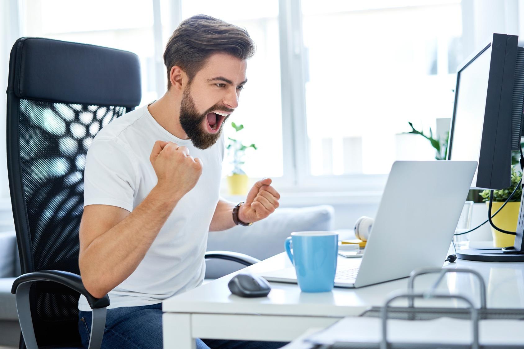 Mitarbeiter am Schreibtisch freut sich über einen erfolgreichen Abschluss.
