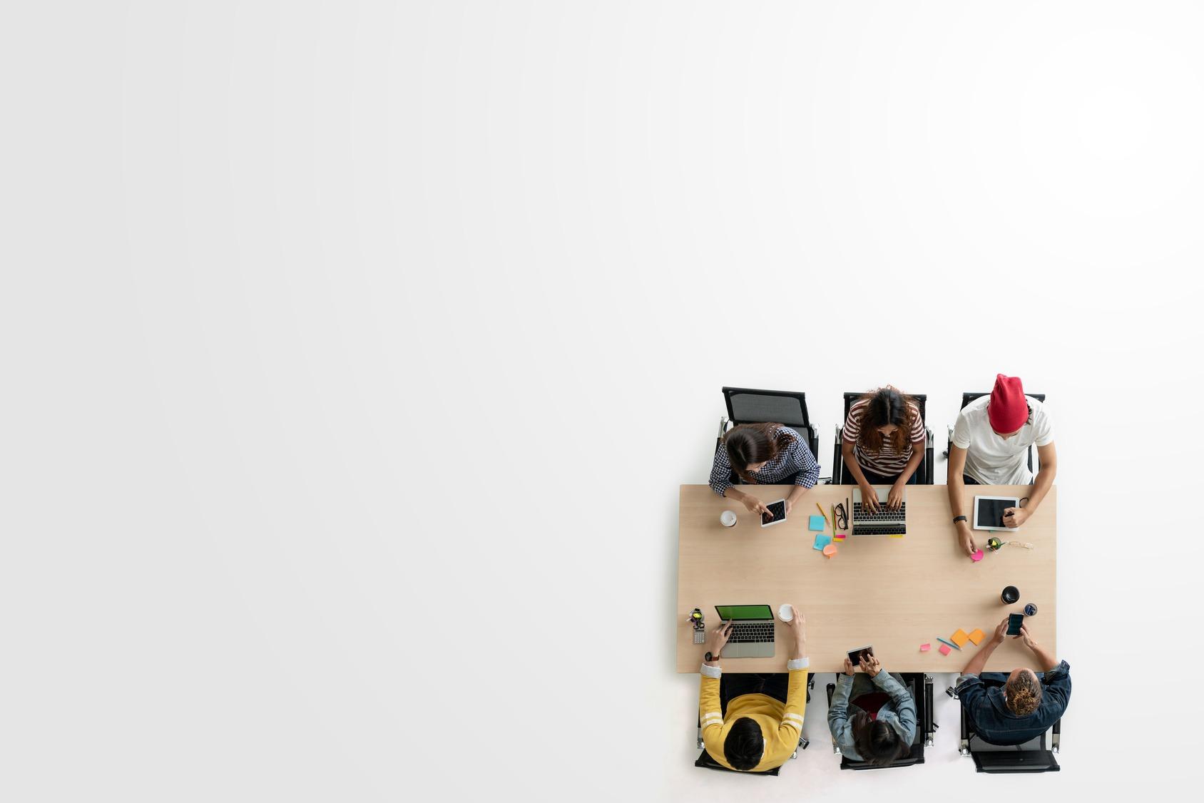Vogelperspektive auf ein sechsköpfiges HR Team an einem Schreibtisch.