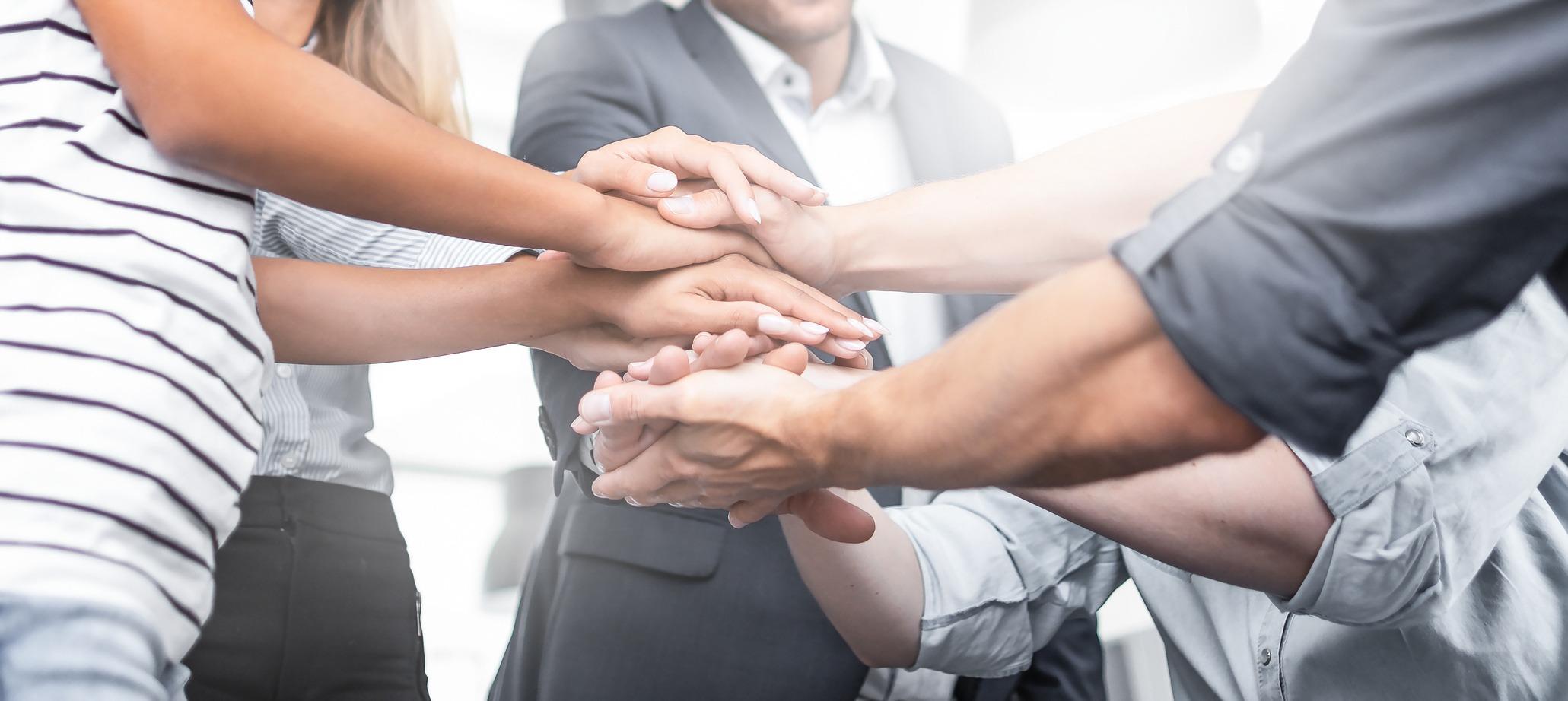 Eine Gruppe Kollegen legt die Hände übereinander.