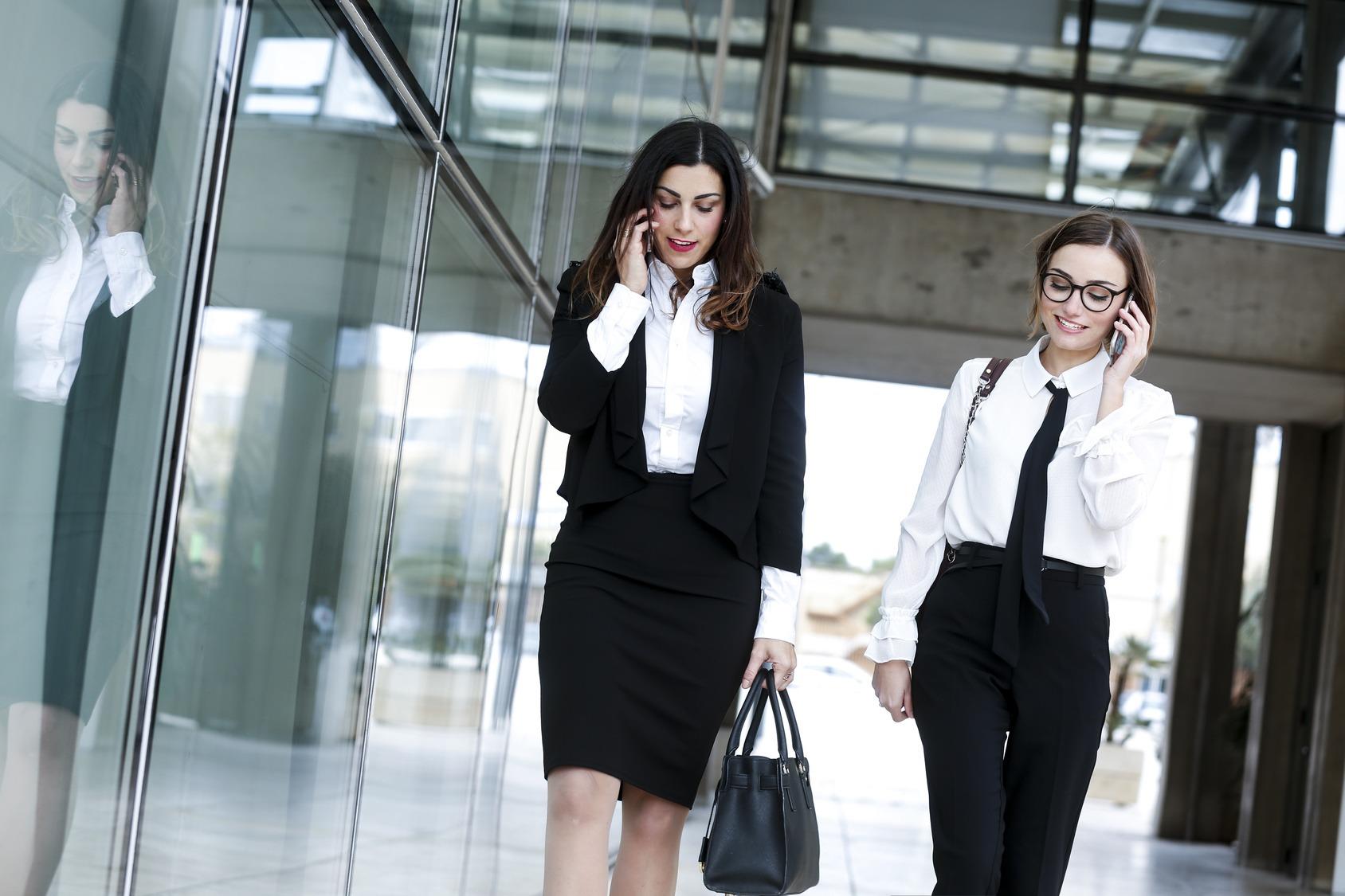 Zwei Bewerberinnen im Business-Look laufen vor einer Glasfassade und telefonieren. Links: Blazer, Bluse, Rock. Rechts: Bluse, Krawatte, Hose.