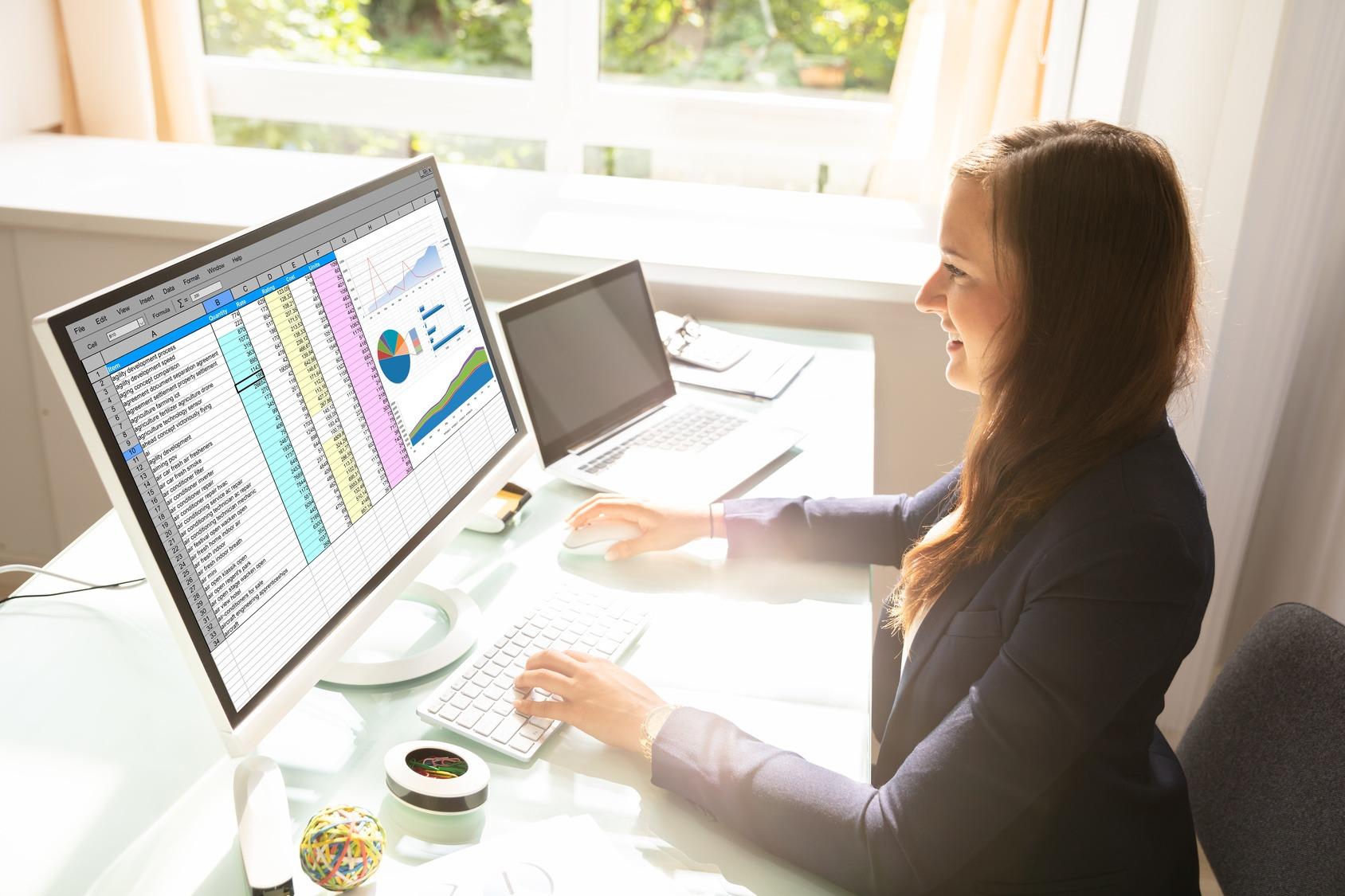 Eine junge Business Analystin sitzt an ihrem Schreibtisch und analysiert die aktuellen Geschäftszahlen.