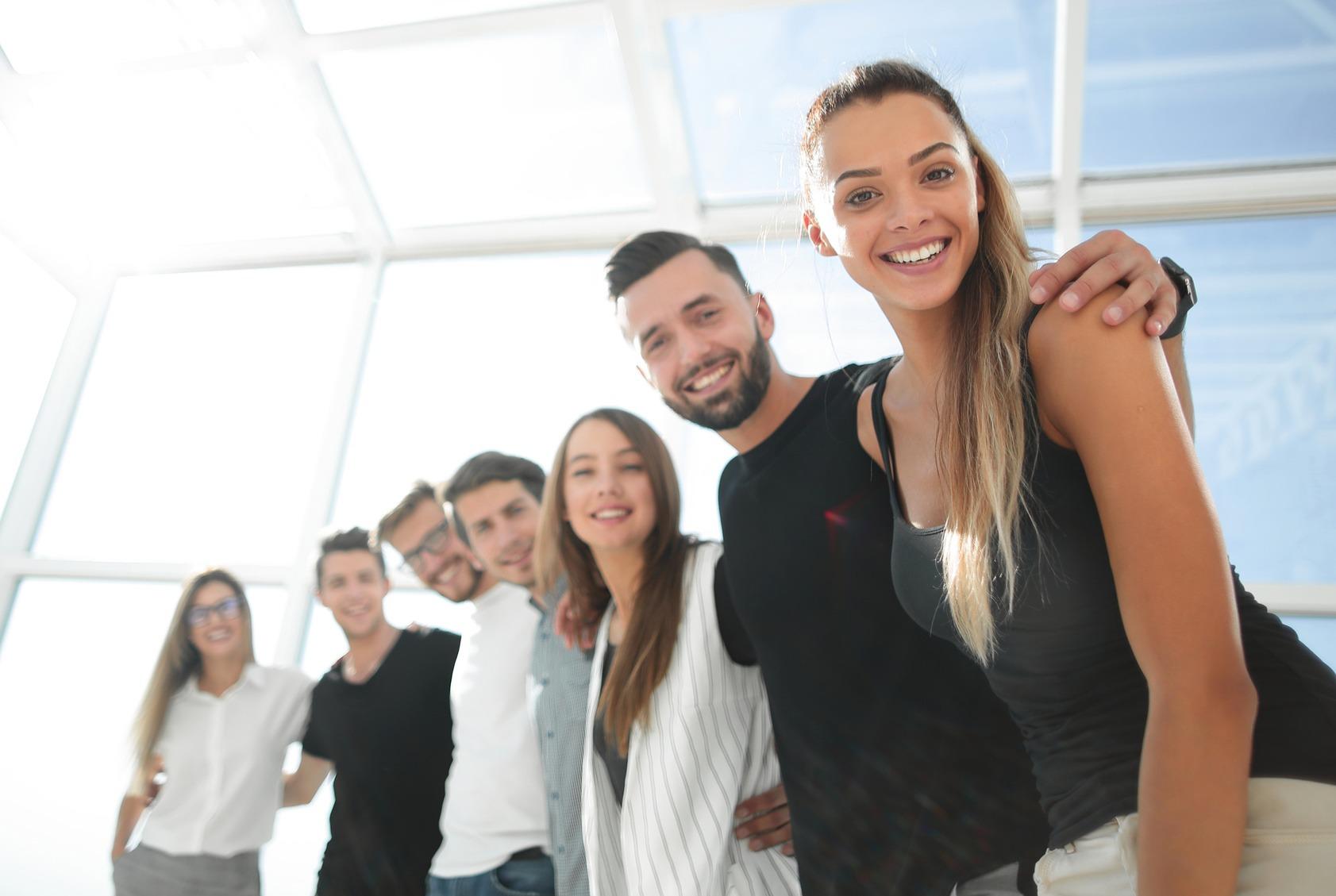 Sieben Teamkollegen stehen lächelnd in ihren neuen Büroräumen.