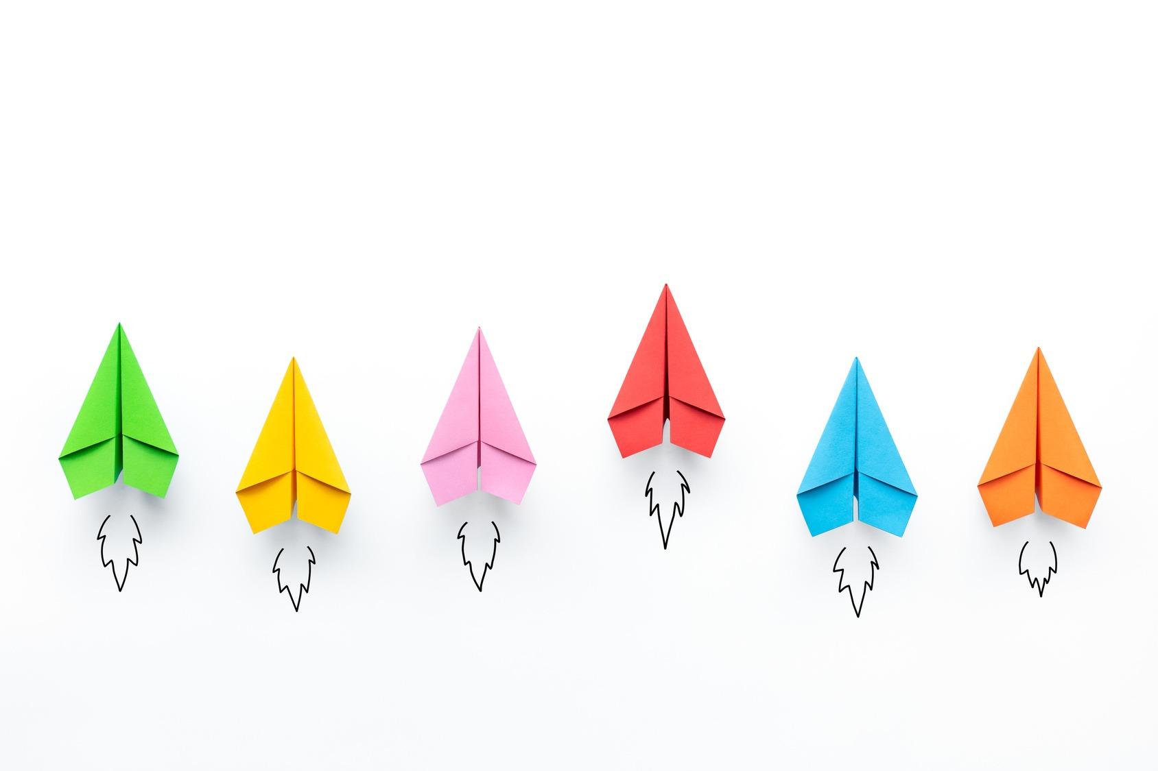 Sechs bunte Papierflieger auf weißem Grund von oben fotografiert.