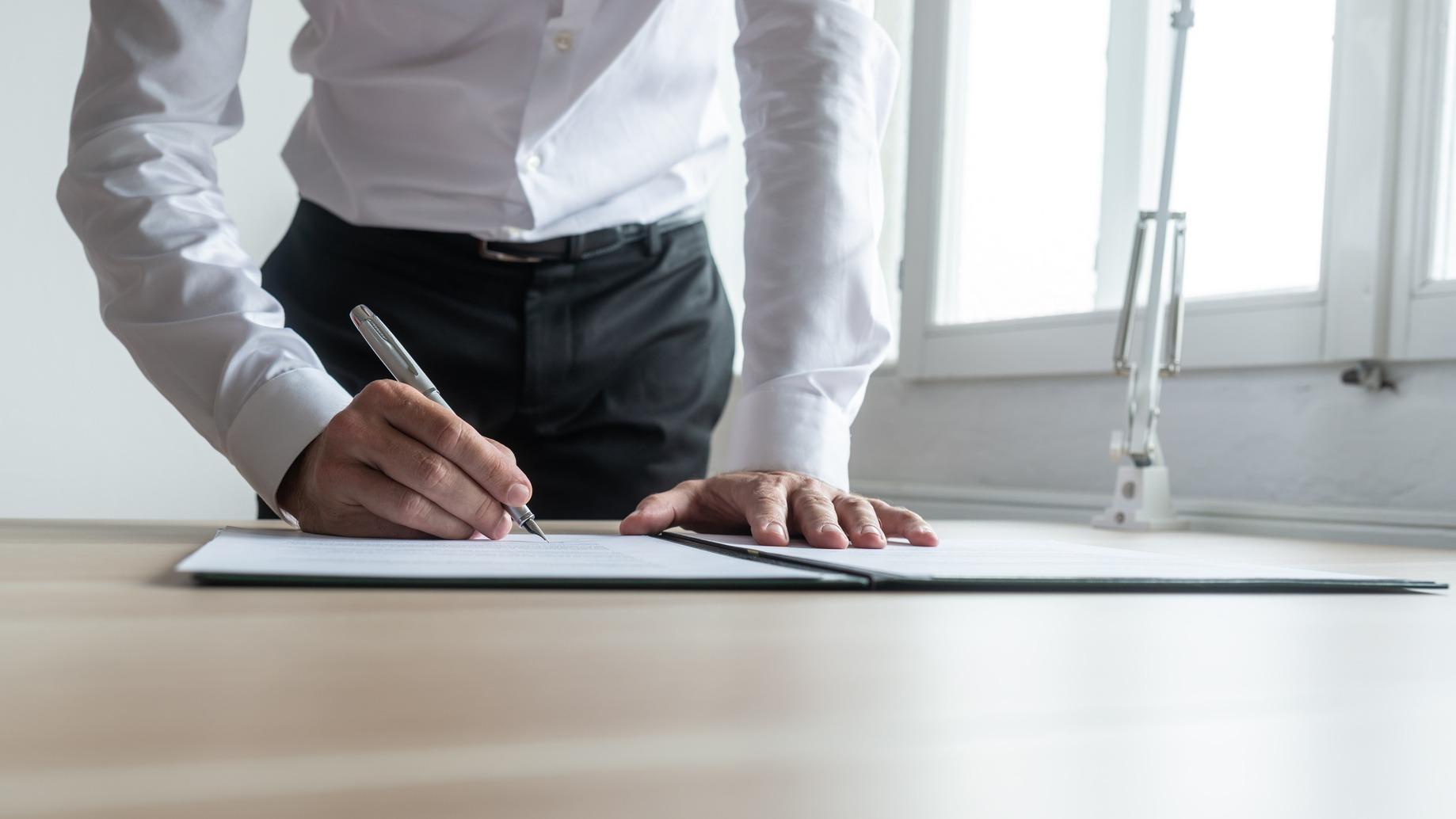 Frontansicht eines Bewerbers der gerade vor einem Tisch steht und einen Arbeitsvertrag unterzeichnet. Der Fokus liegt auf den Händen und dem Vertrag.