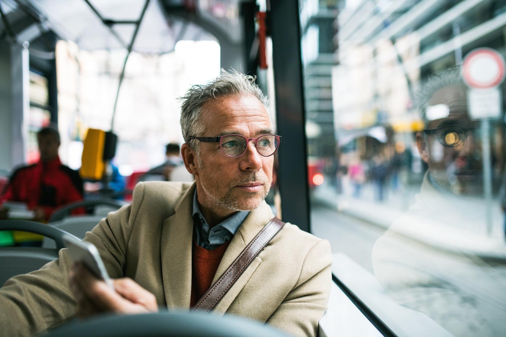 Ein Geschäftsmann sitzt im Elektrobus und meldet gerade eine Beschädigung der Straße über eine spezielle App, an die Stadtverwaltung.