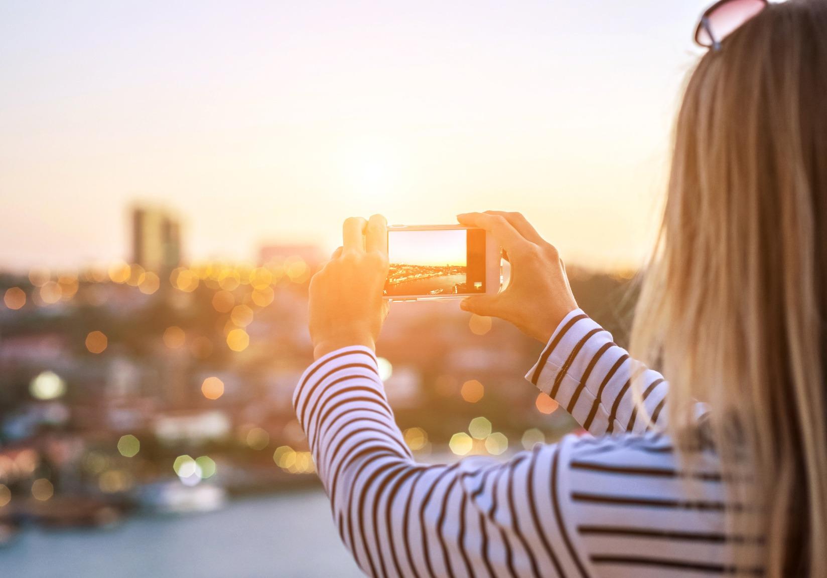 Hellhaarige junge Frau macht ein Foto von einer Smart City mit ihrem Smart Phone.