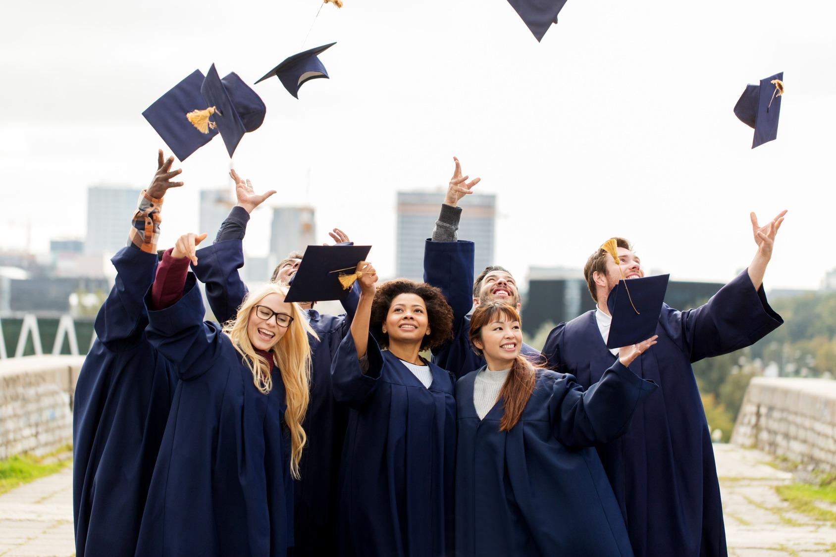Eine Gruppe glücklicher Studenten im Talar. Sie werfen ihren Doktorhut in die Luft.