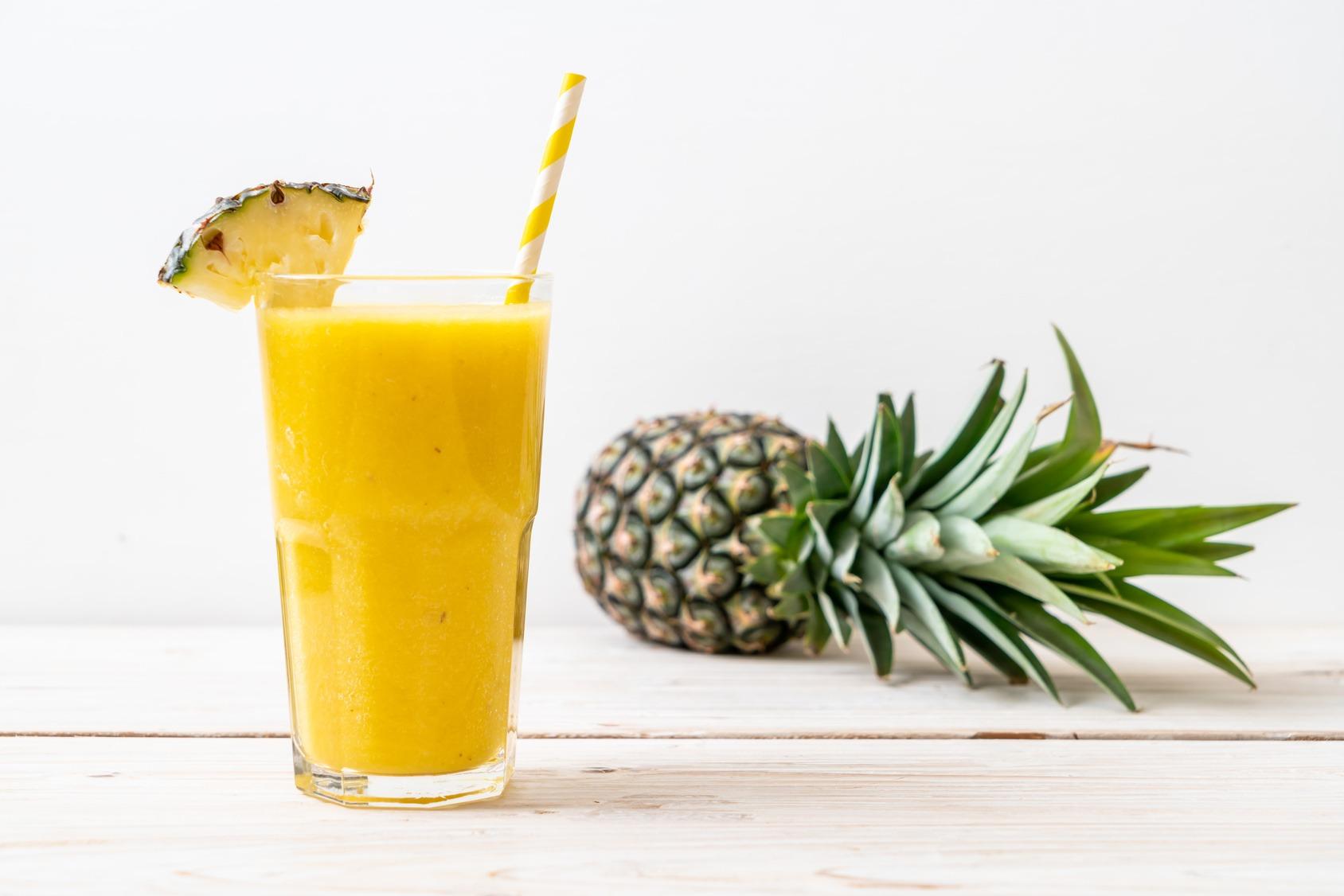 Frischer, selber gemachter Ananassaft in einem Glas mit Röhrchen auf einem hellen Holztisch. Im Hintergrund liegt eine ganze Ananas.