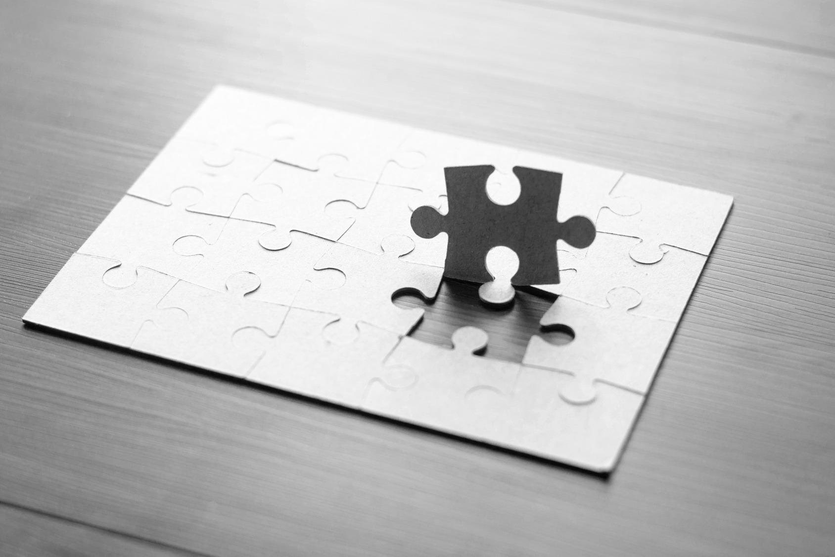 Nahaufnahme von einem Puzzle (5 mal 4 Reihen) auf einem dunklen Holztisch. Die Puzzleteile sind hellgrau und ein Puzzleteil steht aufrecht auf dem Puzzle.
