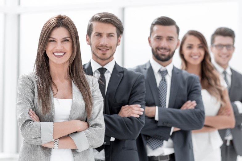 Eine Gruppe Mitarbeiter schaut zufrieden in die Kamera weil ihr Unternehmen Corporate Benefits bietet.