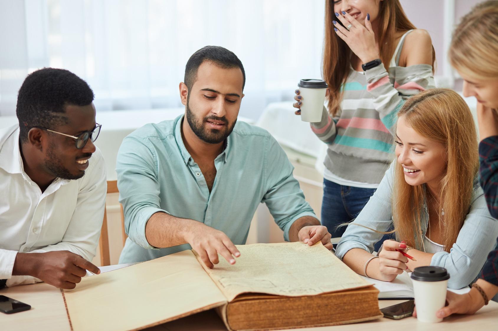 Eine Fünfergruppe Studenten bei der Gruppenarbeit in einer Bibliothek. Vor ihnen auf dem Tisch liegt ein altes Buch.
