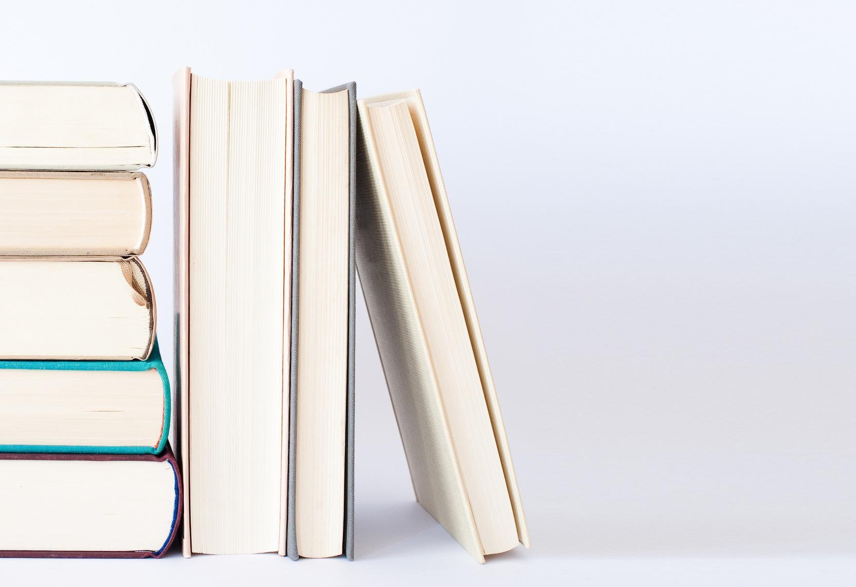 Ein Stapel Bücher vor weißem Hintergrund.