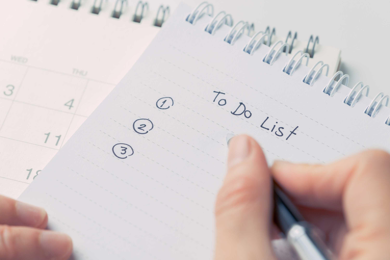 Nahaufnahme einer To Do Liste mit drei offenen Punkten auf der gerade etwas geschrieben wird.
