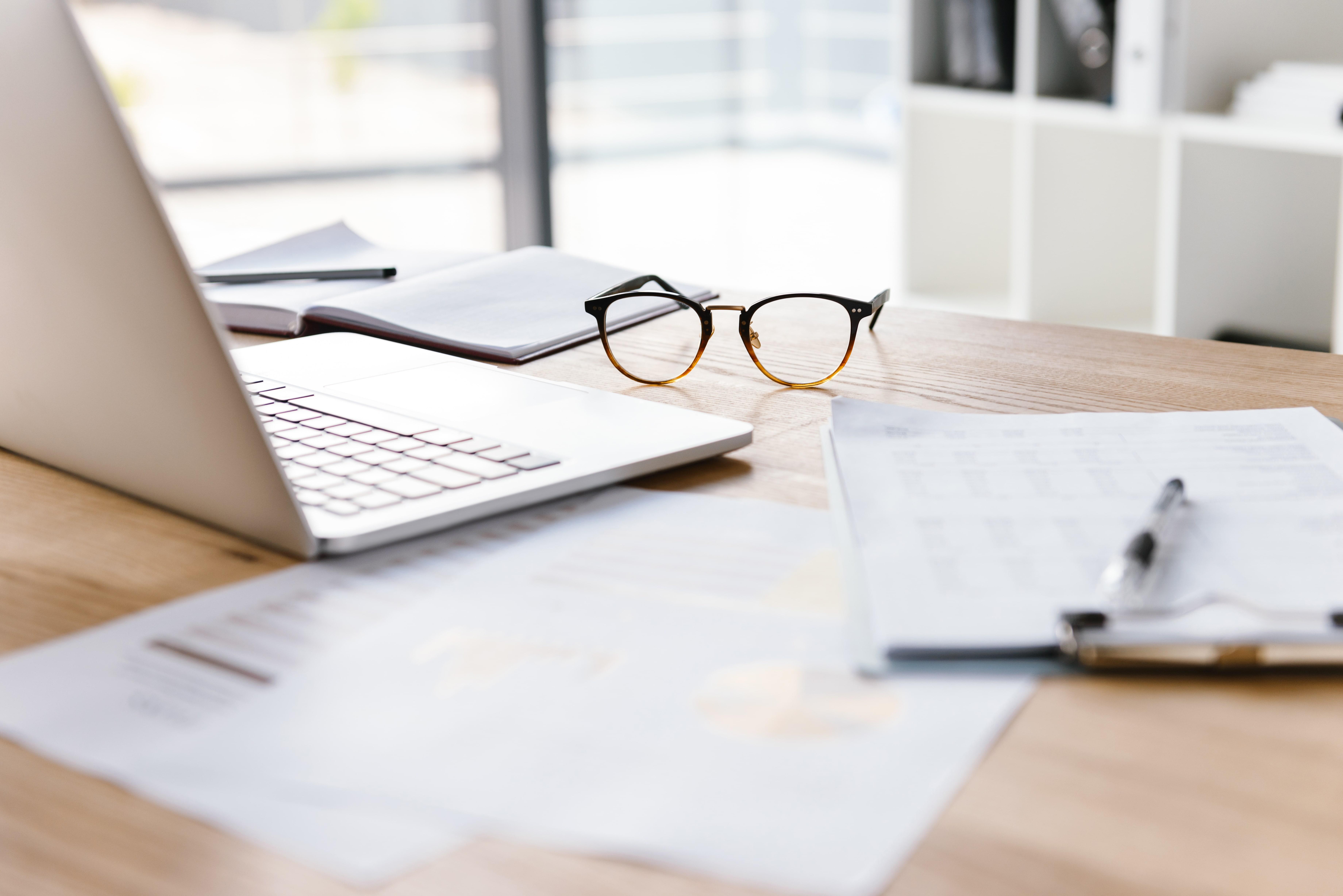 Ein voller Schreibtisch mit Dokumenten, Laptop und einer Brille.