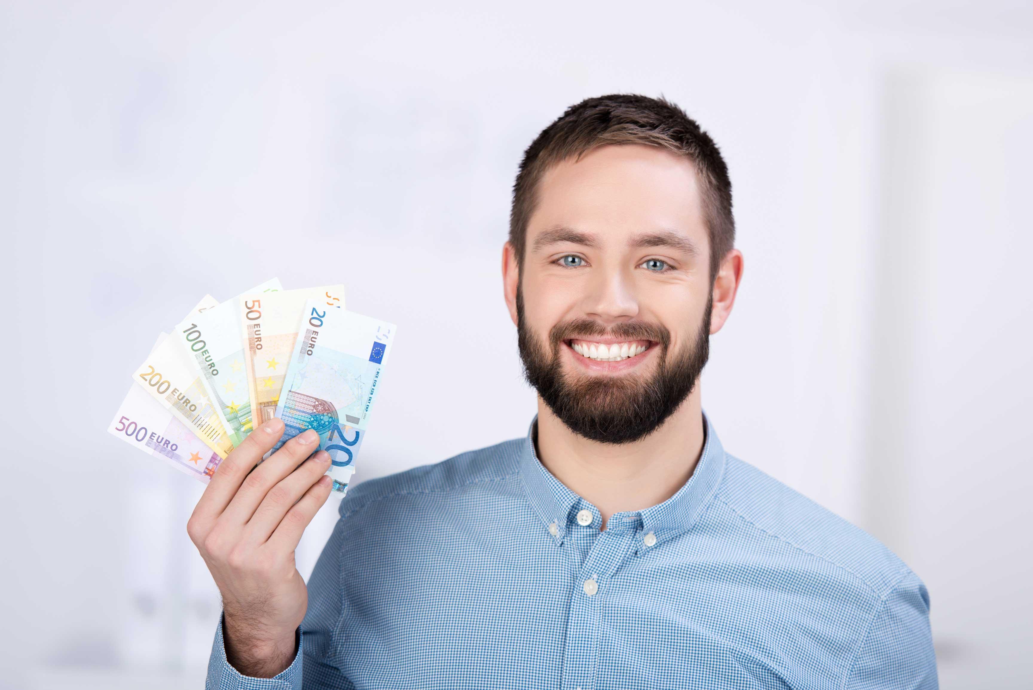 Junger Student mit hält ein Bündel Geldscheine nach oben und freut sich.