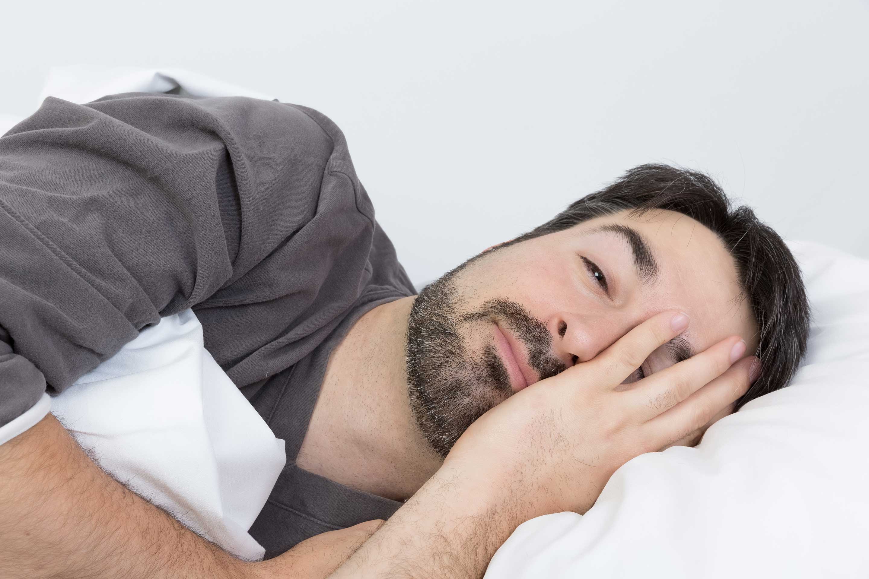 Mann mir Schlafproblemen liegt erschöpft im Bett.