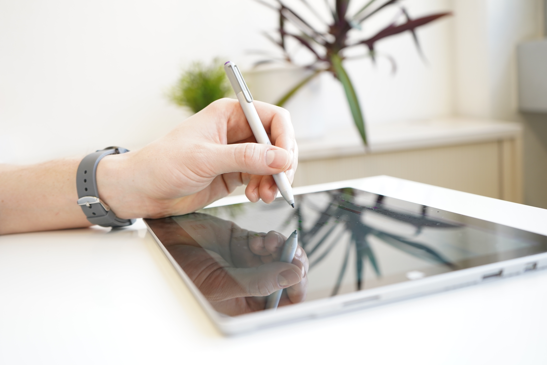 Tablet auf weißem Tisch auf dem gerade mit einem Eingabestift geschrieben wird.