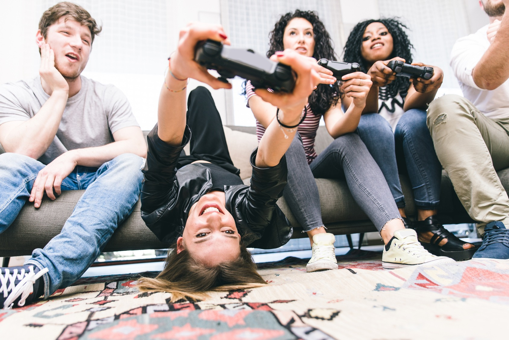 Eine Gruppe Studenten beim gemeinsamen zocken auf der Couch.
