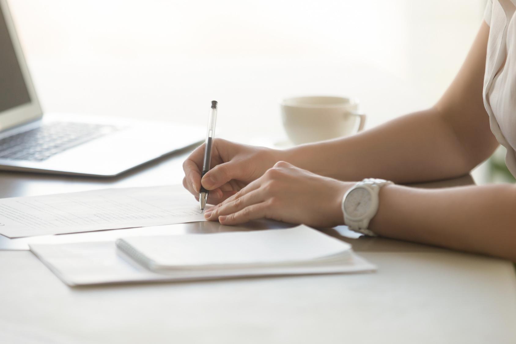 Eine Bewerberin unterzeichnet ihren Arbeitsvertrag beim Abschluss ihres Vorstellungsgesprächs.