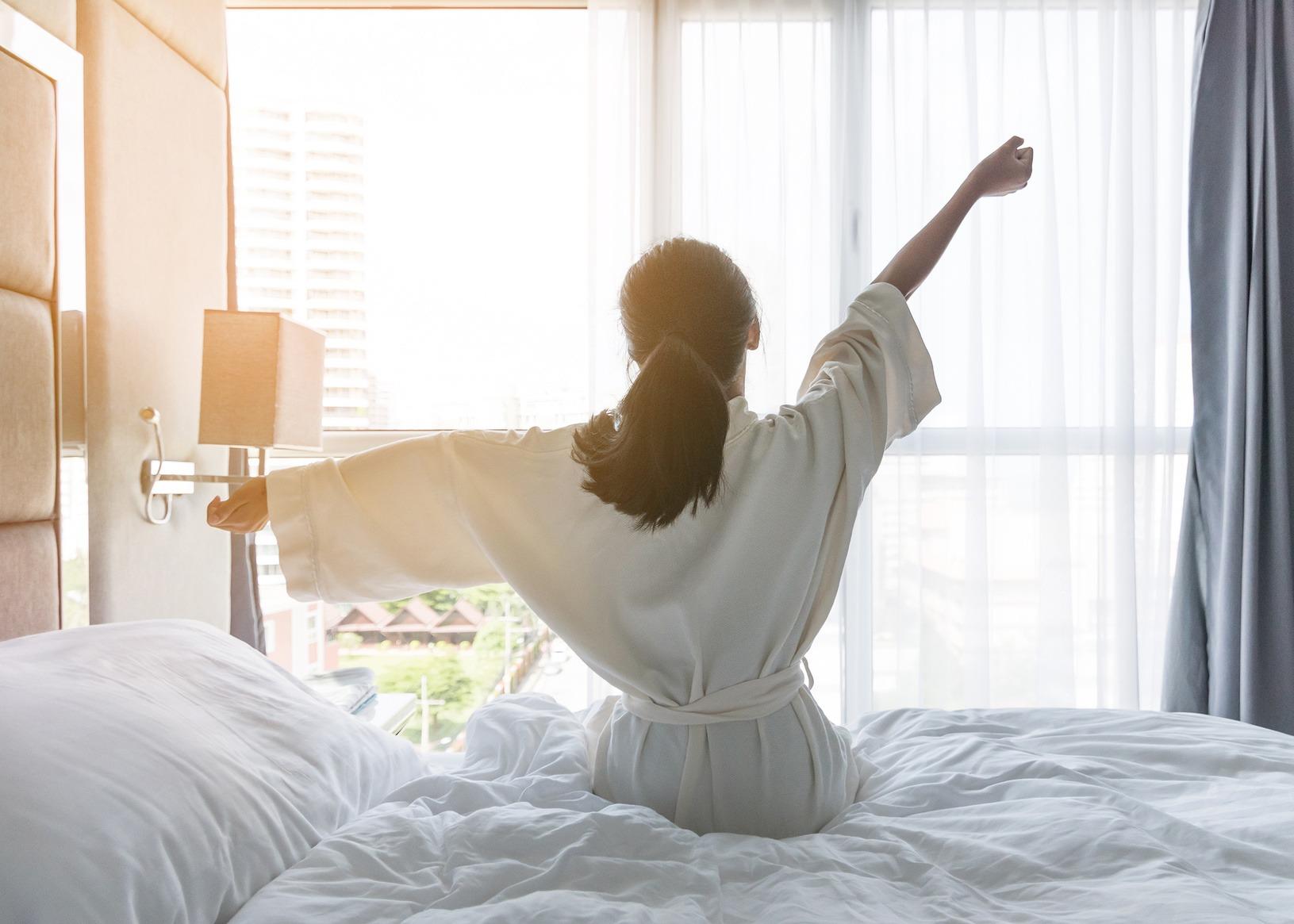 Eine junge Frau sitzt nach dem Aufstehen auf der Bettkante und streckt sich. Ausreichend Schlaf gehört für sie zu einer erfolgreichen Work Life Integration.