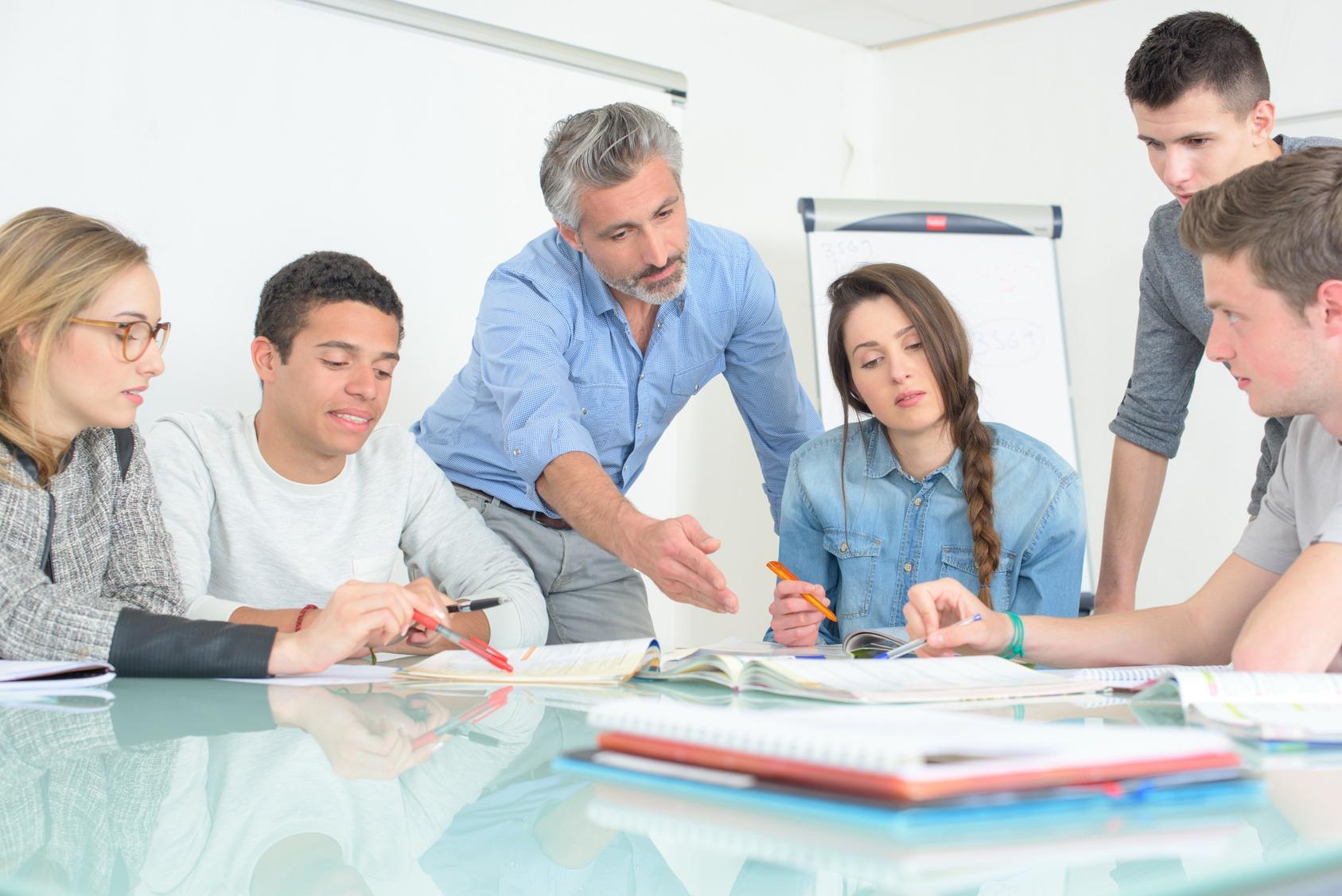 Eine Gruppe Non-graduates und ein Trainer bei einer Schulung.