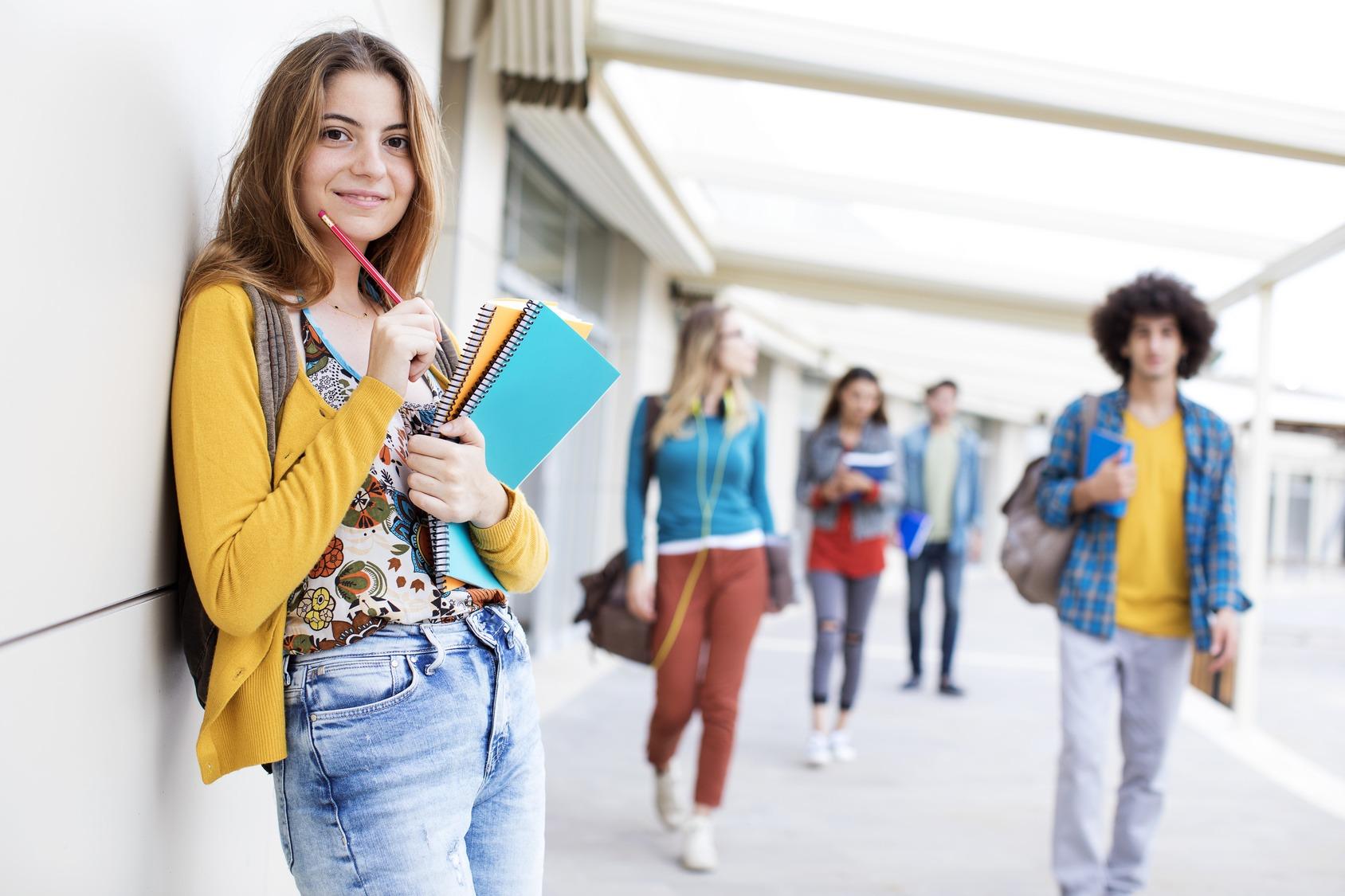 Eine Gruppe von fünf jungen Studenten in einem urbanen Setting. Vier der Studenten sind unscharf im Hintergrund und bewegen sich auf den Betrachter zu, eine Studentin im Vordergrund lehnt an einer Mauer und hat einen Stapel Dokumente unter dem Arm. SIe schaut freundlich zum Betrachter.