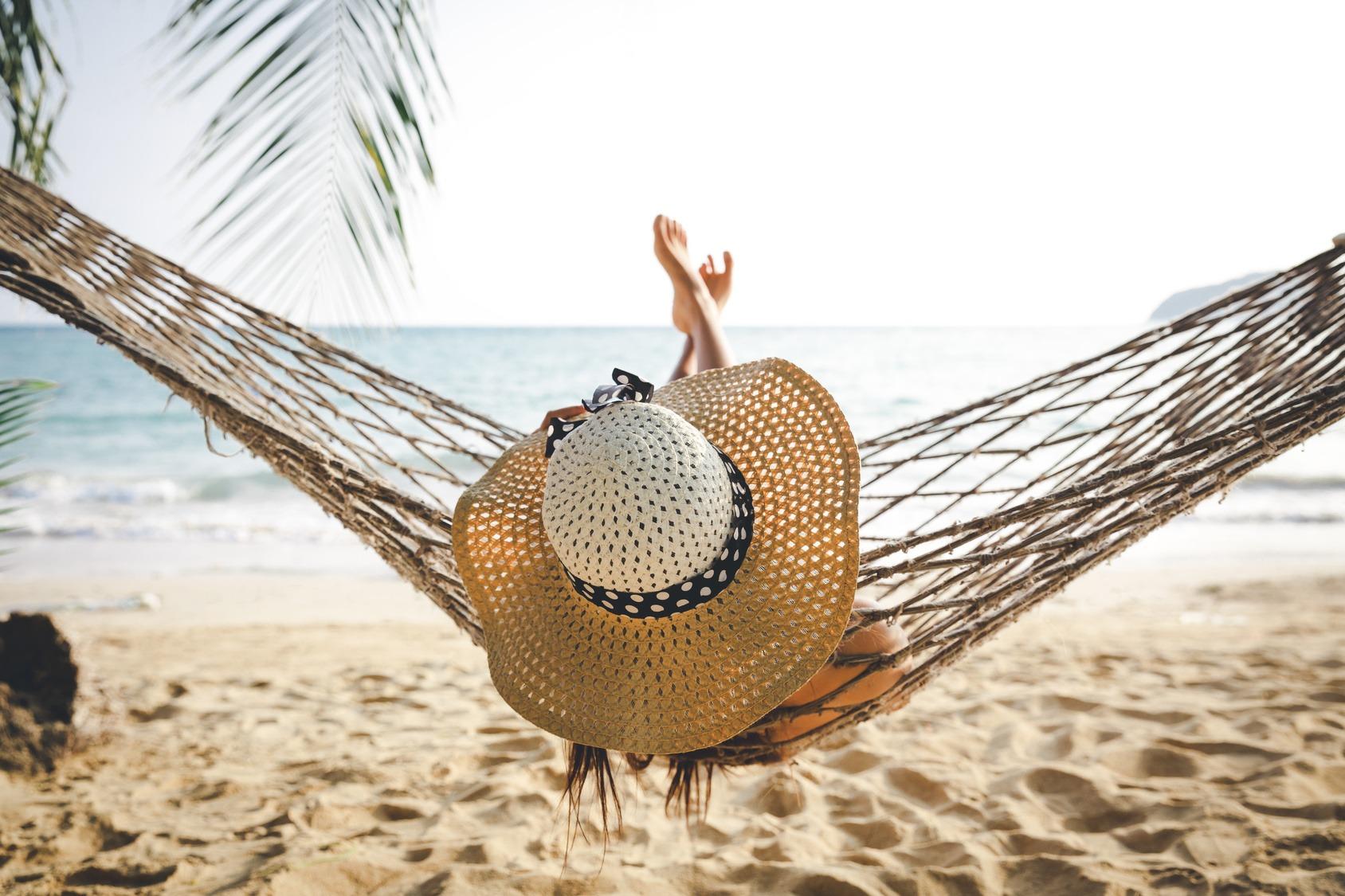 Eine junge Frau mit Strohhut liegt quer in einer Hängematte am Strand.