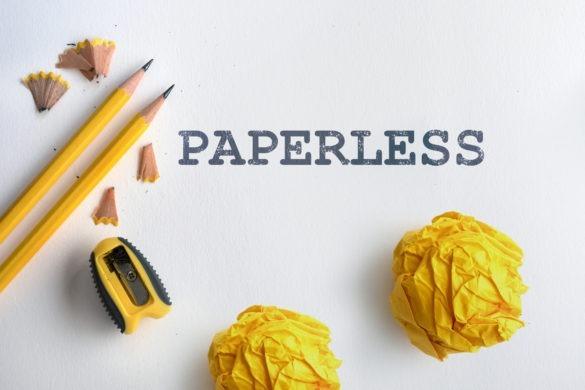 PAPERLESS Schriftzug auf weißem Papier umgeben von Bleistiften, Spitzer und zerknülltem gelbem Papier.