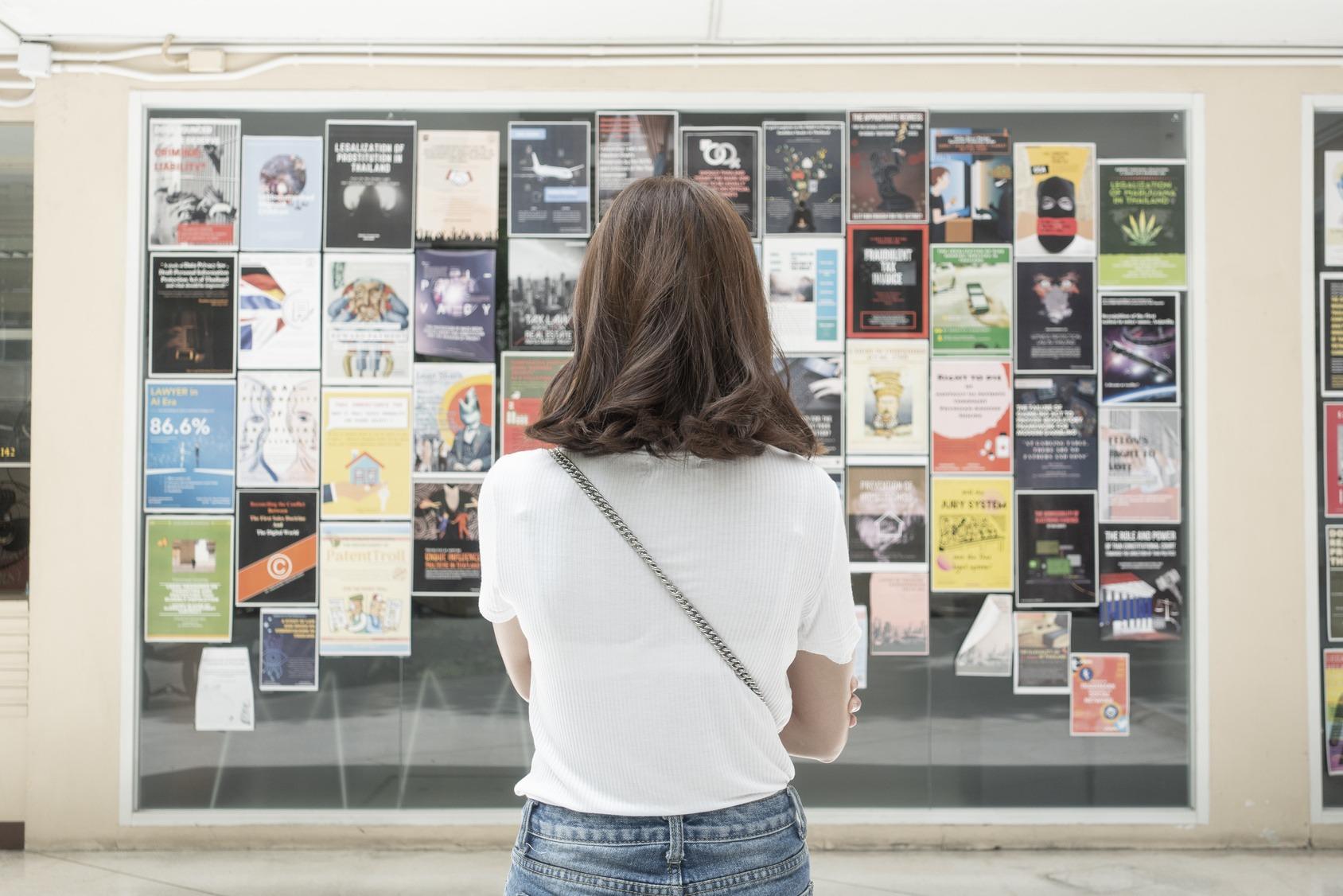 Eine junge Studentin steht vor einer Anzeigetafel an ihrer Hochschule.
