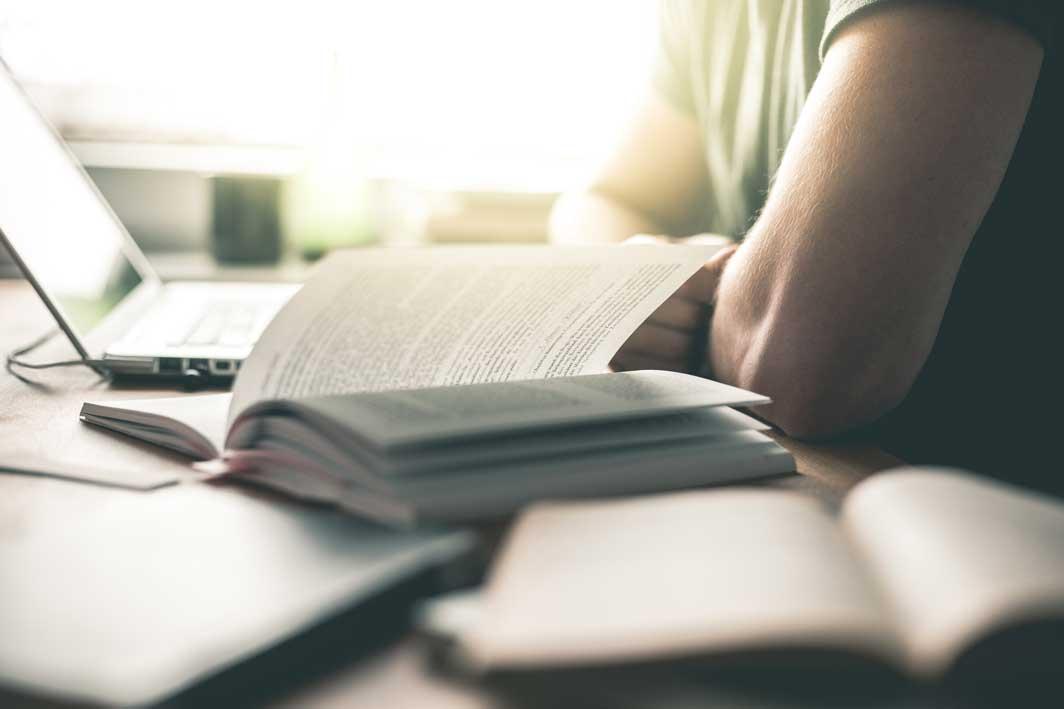 Ein junger Student sitzt vor seinem Laptop und lernt für eine wichtige Prüfung. Er ist umgeben von zahlreichen Büchern.
