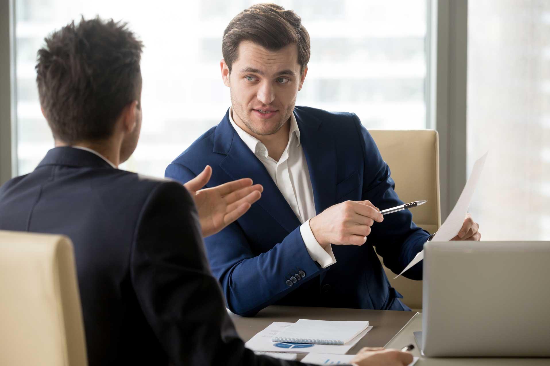 Ein junger Bewerber sitzt im Vortsellungsgespräch und stellt dem Personaler gegenüber eine interessante Rückfrage.