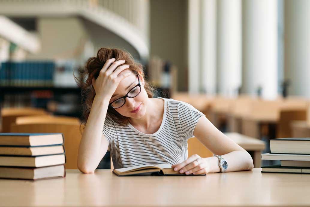Eine junge Studentin sitzt in der Bibliothek und lernt für eine wichtige Prüfung. Um sie herum steht ein Stapel Bücher.