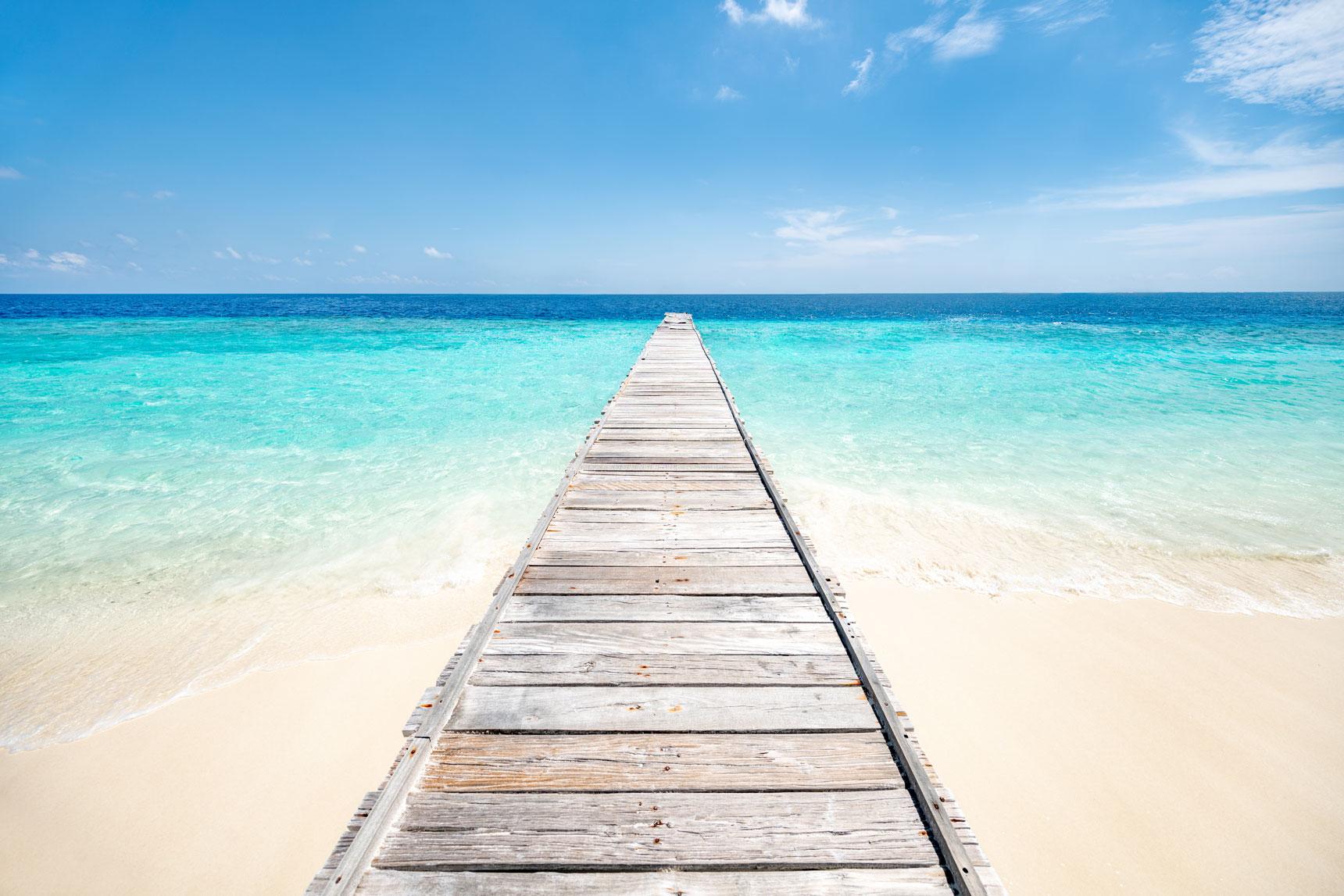 Ein Bootssteg führt vom weissen Sandstrand aufs tuerkisblaue Meer.