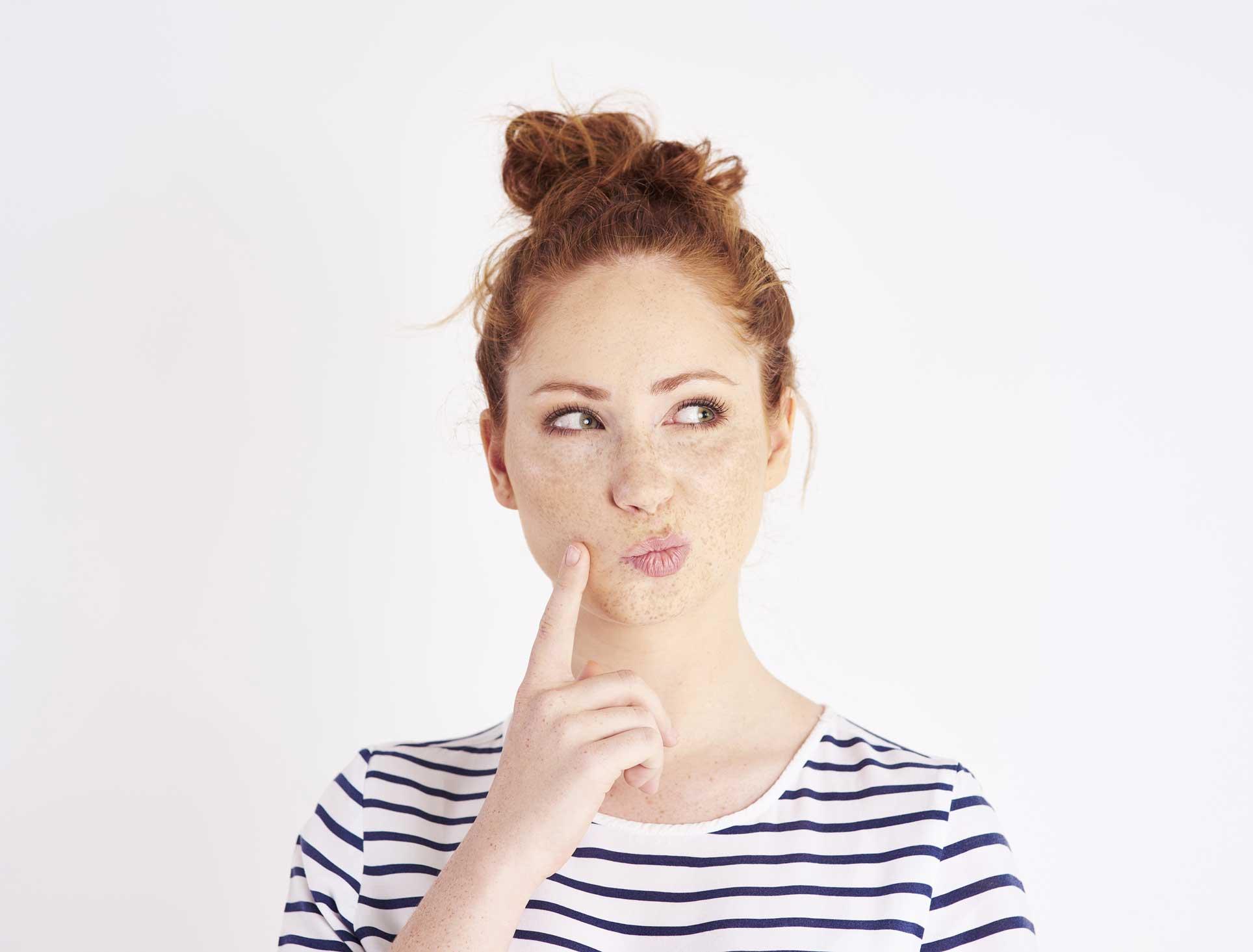 Junge rothaarige Bewerberin hält ihren Zeigefinger an die Wange und blickt zur Seite. Sie überlegt sich eine sinnvolle Rückfrage.