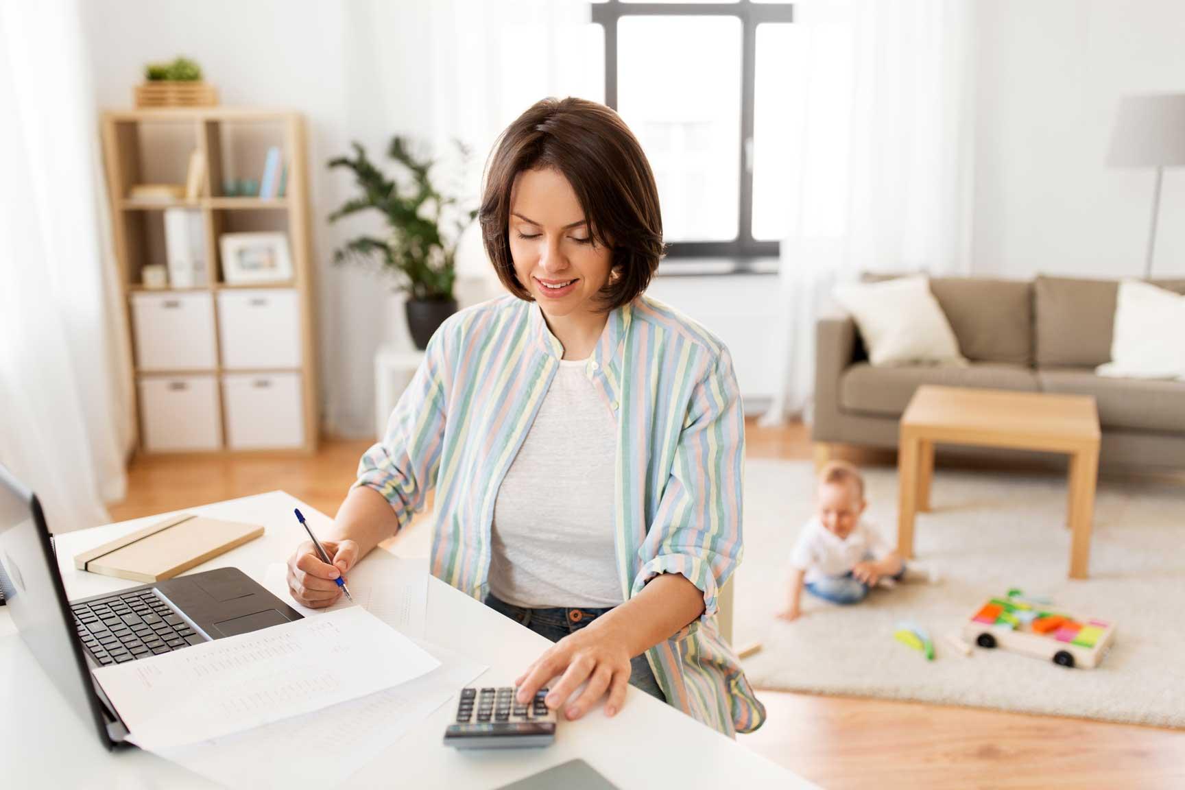 Junge Mutter mit Kind arbeitet dank flexibler Arbeitszeiten von Zuhause aus.