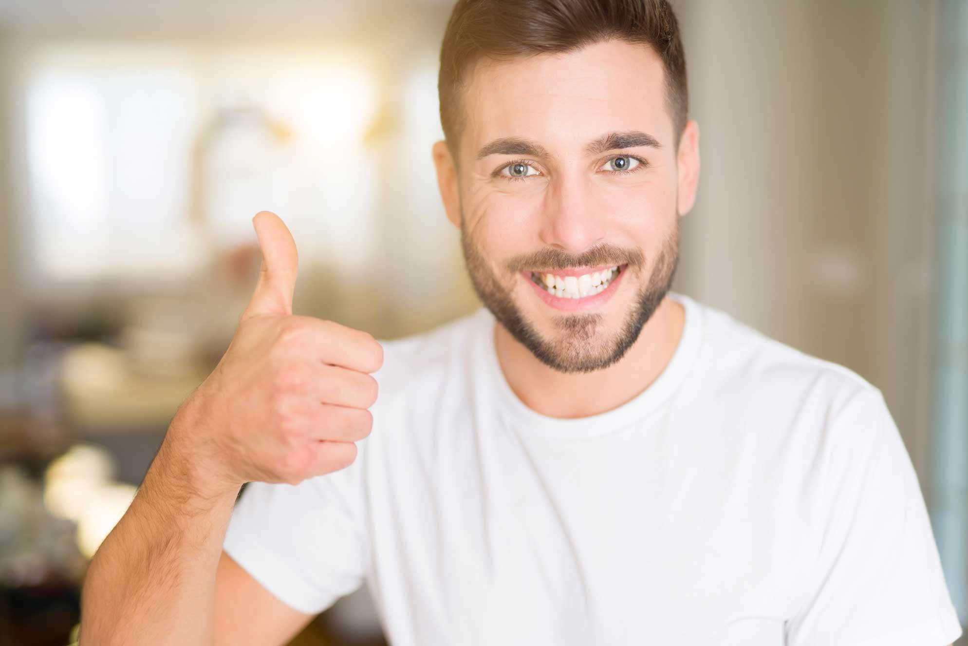 Ein zufriedener Bewerber zeigt die Thumps-up Geste und freut sich über ein erfolgreiches Vorstellungsgespräch.