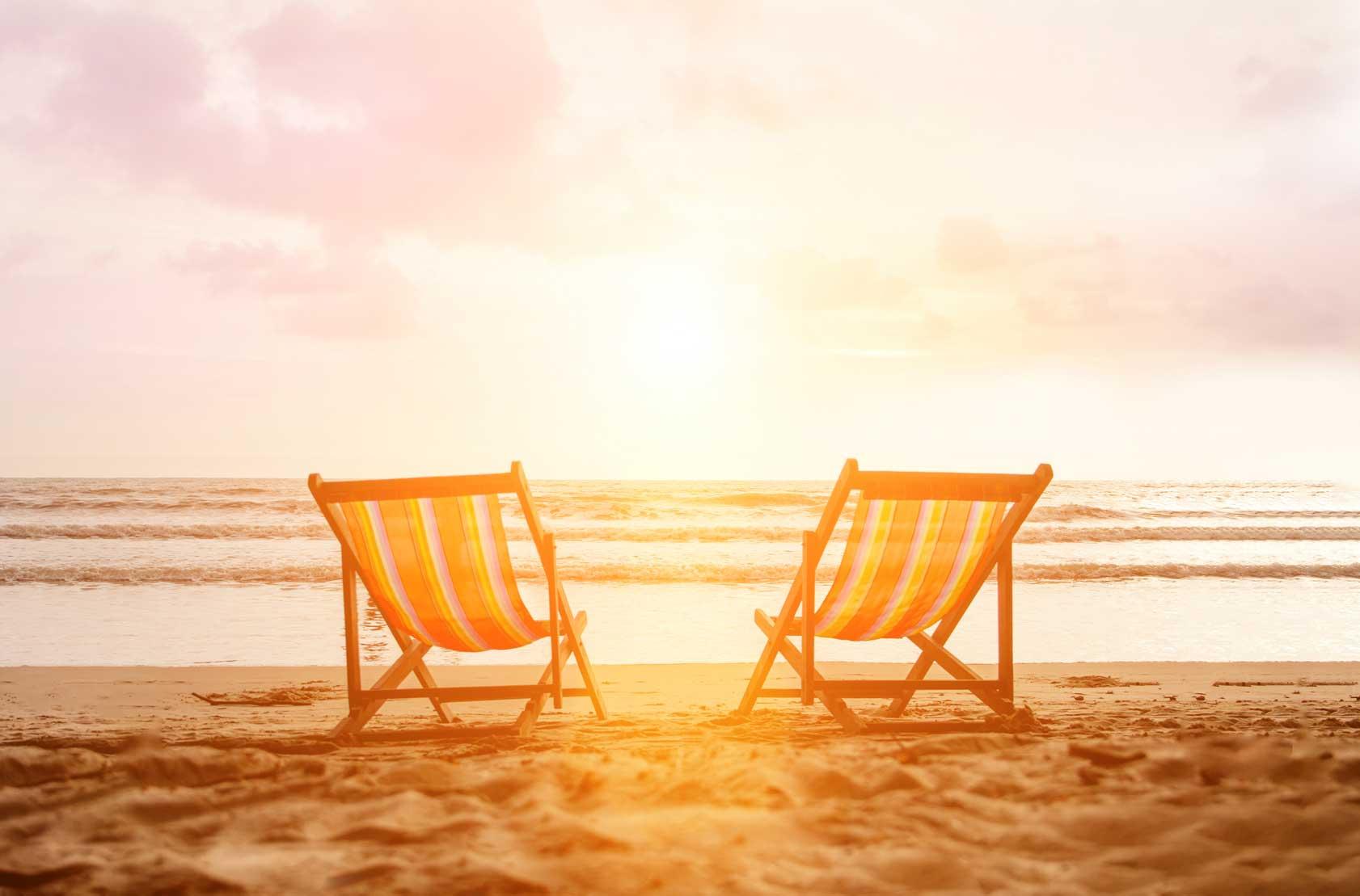Zwei in Richtung Meer ausgerichtete Strandstühle stehen bei Sonnenaufgang am Strand.