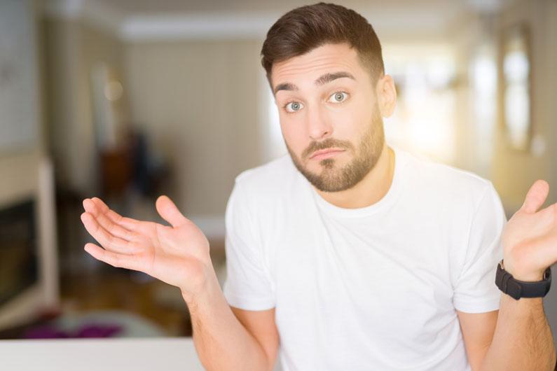 Junger Bewerber macht die Shruggie Geste weil er nicht weiss was er fragen soll.