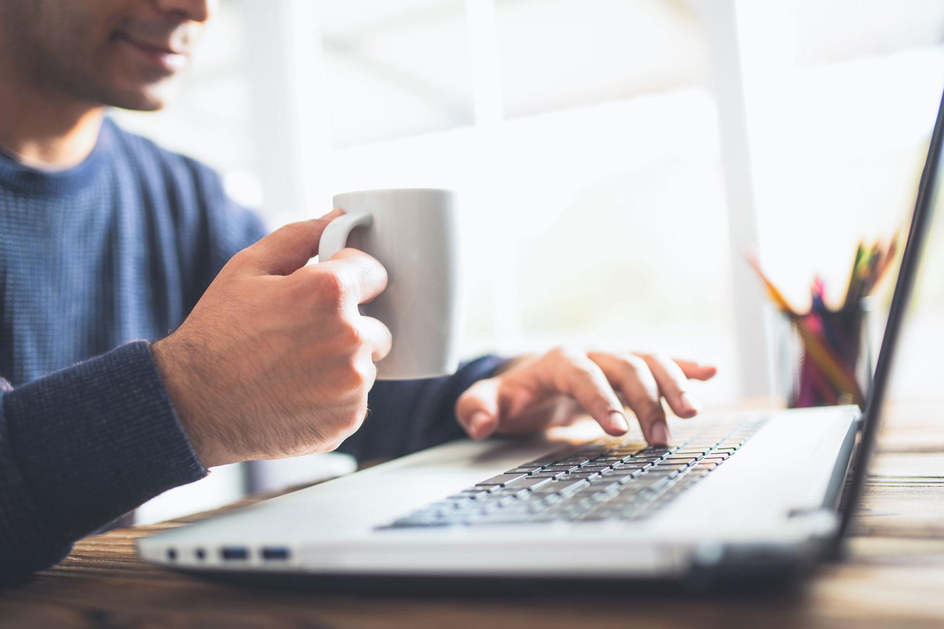 Ein Bewerber sitzt mit einer Tasse Kaffee in der Hand vor seinem Laptop.