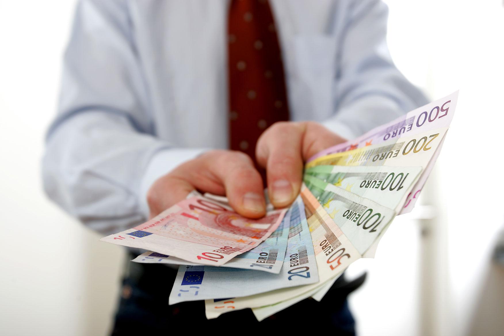 Ein Geschäftsmann hält ein Bündel Euro Scheine ins Zentrum des Bilds.
