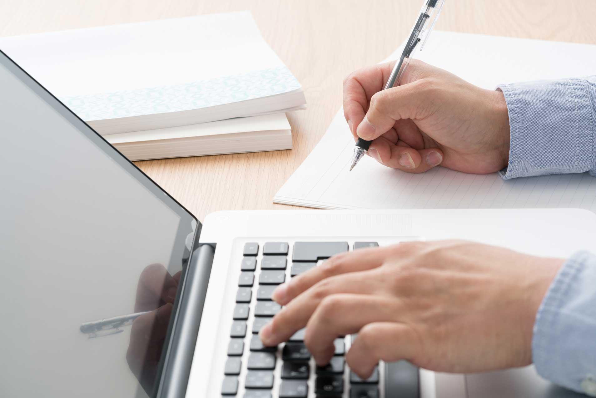 Ein Mitarbeiter sitzt mit dem einem Notizblock und einem Laptop am Schreibtisch. das Bild zeigt eine Nahaufnahme seiner Hände.