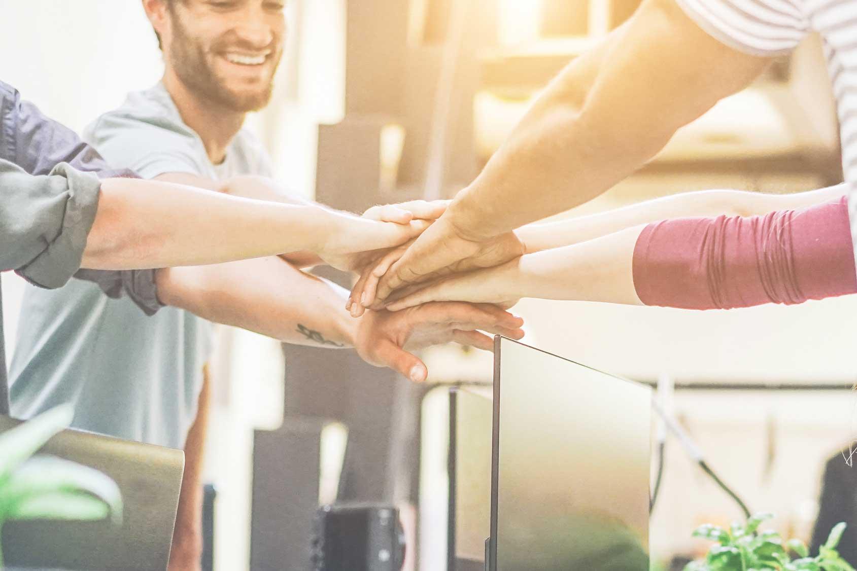 Zentraler Punkt des Bildes ist ein Stapel zusammengelegter Hände. Ritual zur Teammotivation.