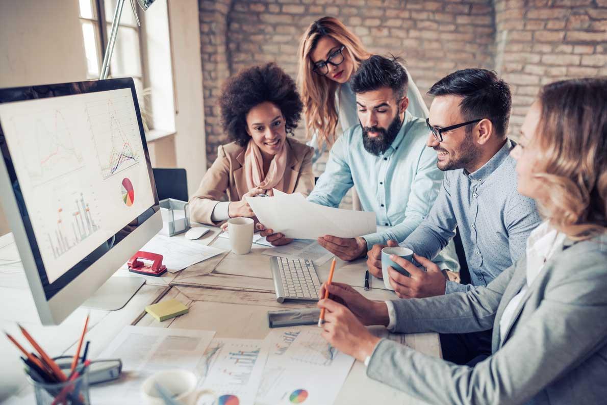 Arbeitskollegen sitzen gemeinsam an einem Arbeitsplatz und besprechen ein Teamprojekt.